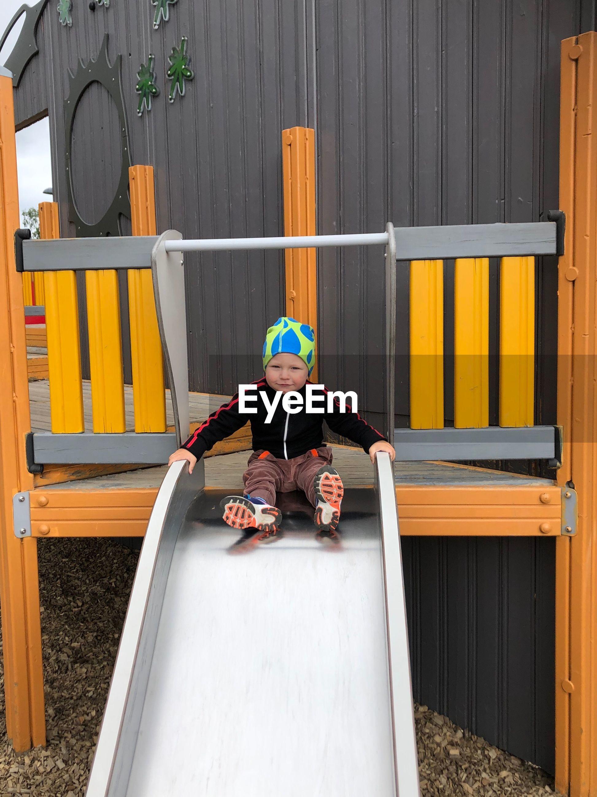 Portrait of boy sitting on slide at playground