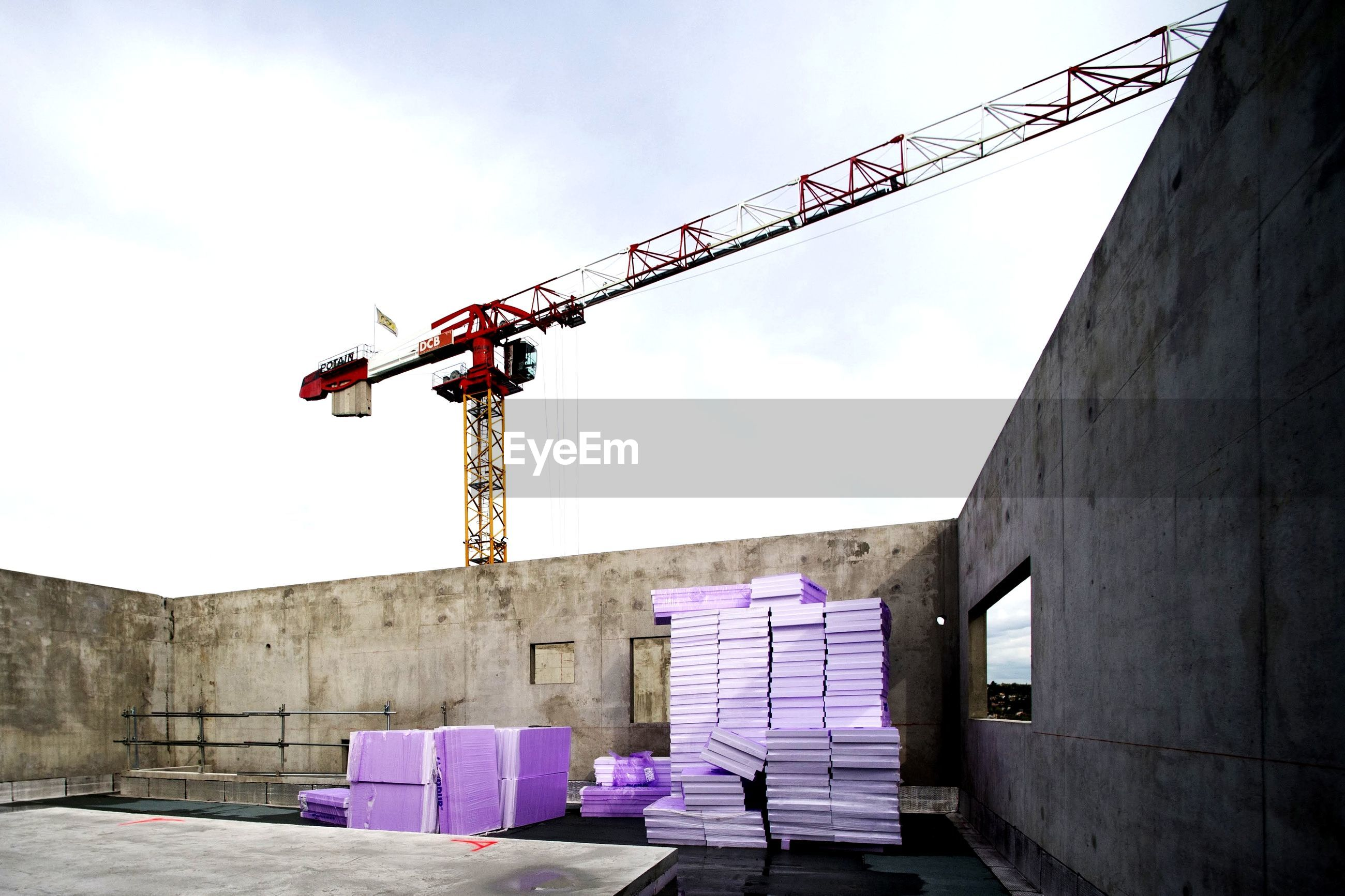 LOW ANGLE VIEW OF CRANE AGAINST BUILDING WALL
