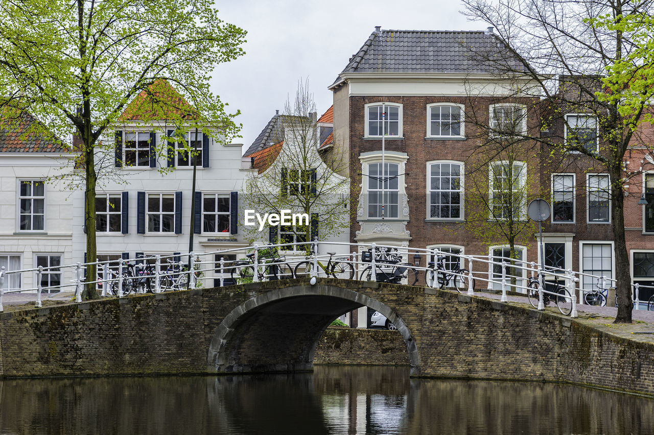 built structure, architecture, building exterior, building, water, bridge, tree, connection, bridge - man made structure, plant, river, waterfront, nature, arch, residential district, reflection, transportation, city, no people, outdoors, arch bridge, row house