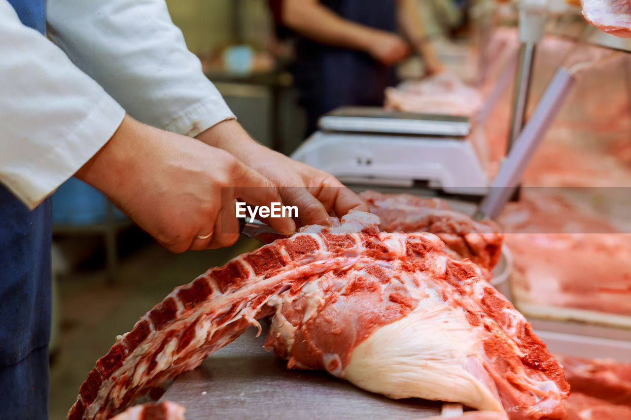 Midsection Of Butcher Cutting Meat On Table At Shop