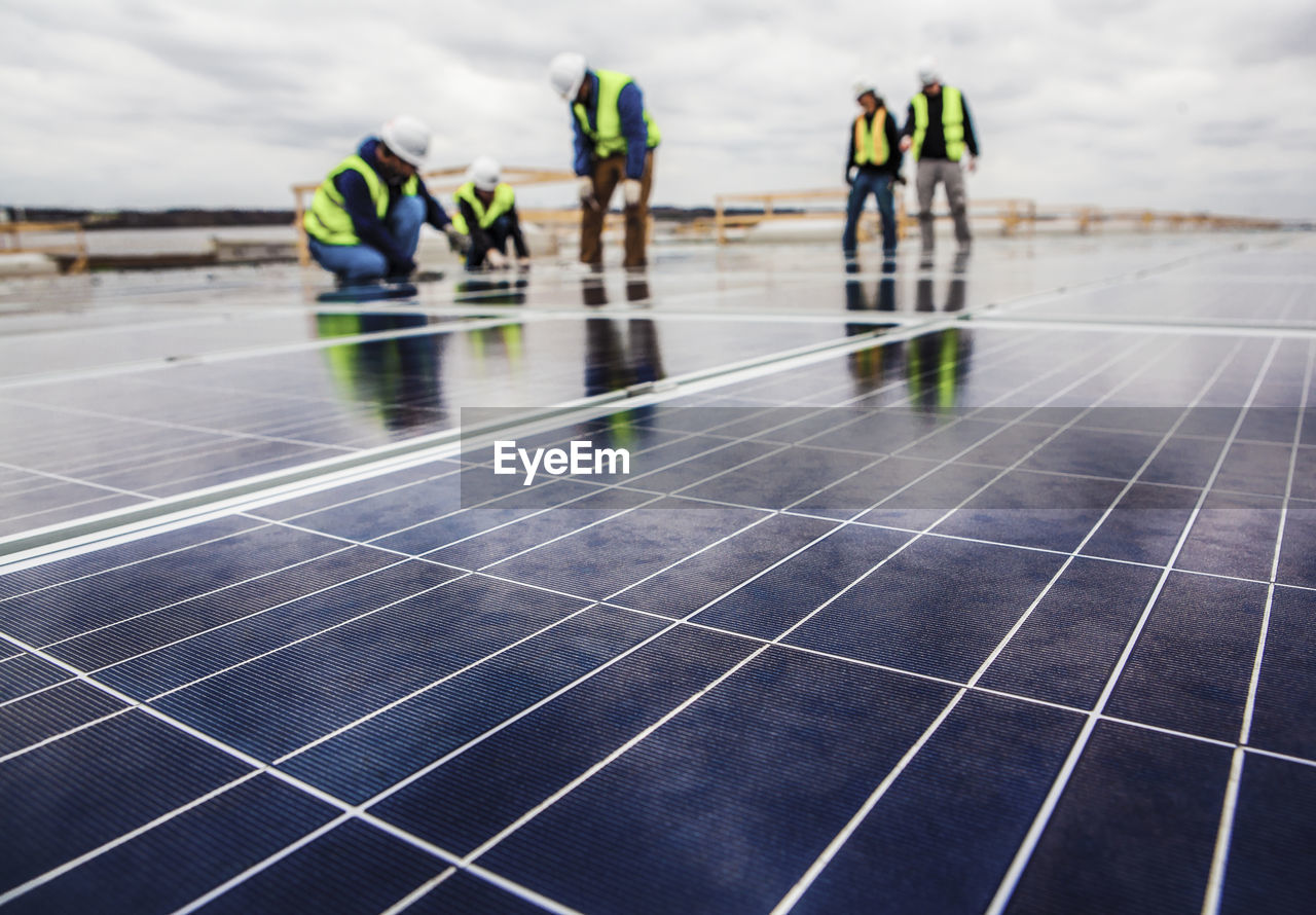 renewable energy, group of people, fuel and power generation, alternative energy, environmental conservation, sky, solar panel, solar energy, nature, real people, day, focus on foreground, technology, environment, men, lifestyles, outdoors, architecture, people, walking, sustainable resources