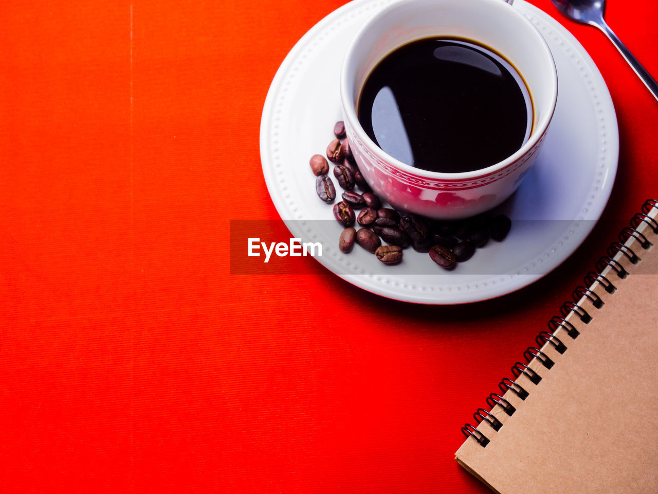 food and drink, drink, coffee, cup, coffee - drink, coffee cup, mug, refreshment, red, saucer, indoors, high angle view, crockery, table, still life, no people, spiral notebook, black coffee, copy space, freshness, black tea, non-alcoholic beverage, tea cup