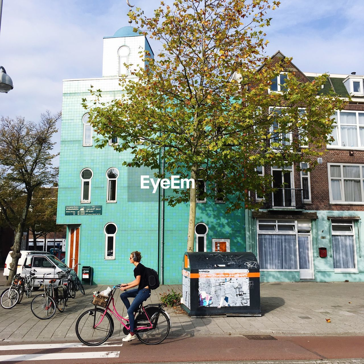 MAN RIDING BICYCLE ON STREET AGAINST BUILDINGS