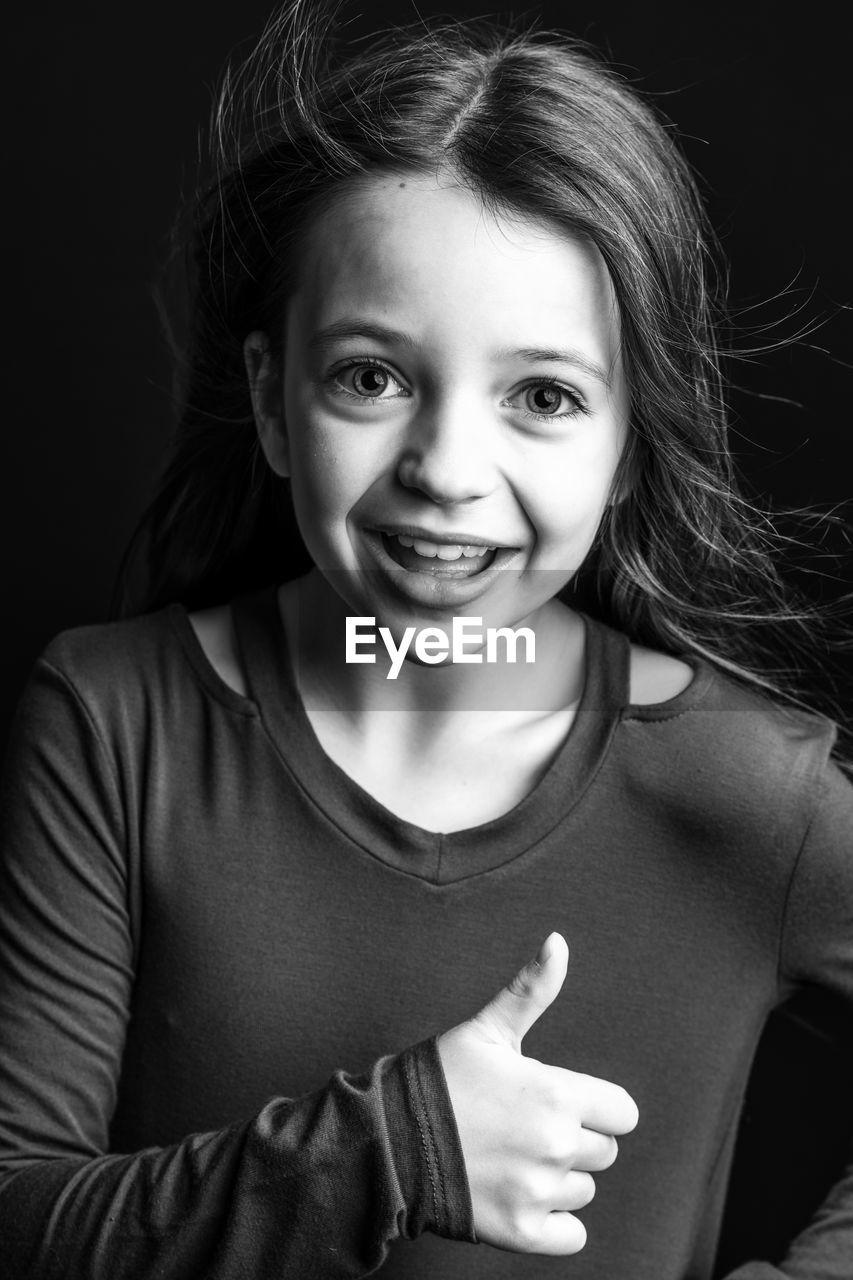 Portrait of cute girl against black background