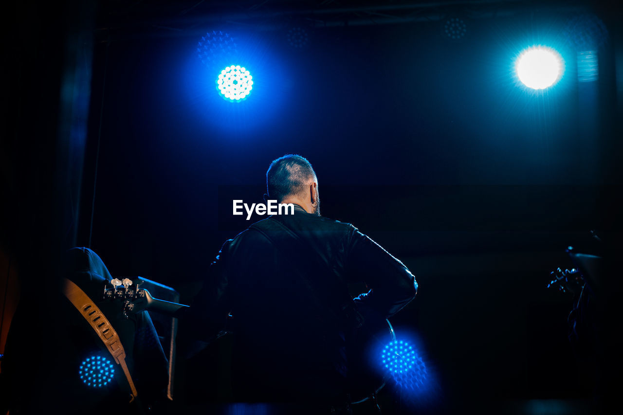 one person, illuminated, lighting equipment, real people, performance, stage, stage - performance space, indoors, arts culture and entertainment, stage light, waist up, performing arts event, rear view, artist, men, light, musician, microphone, input device, nightlife, skill, concert