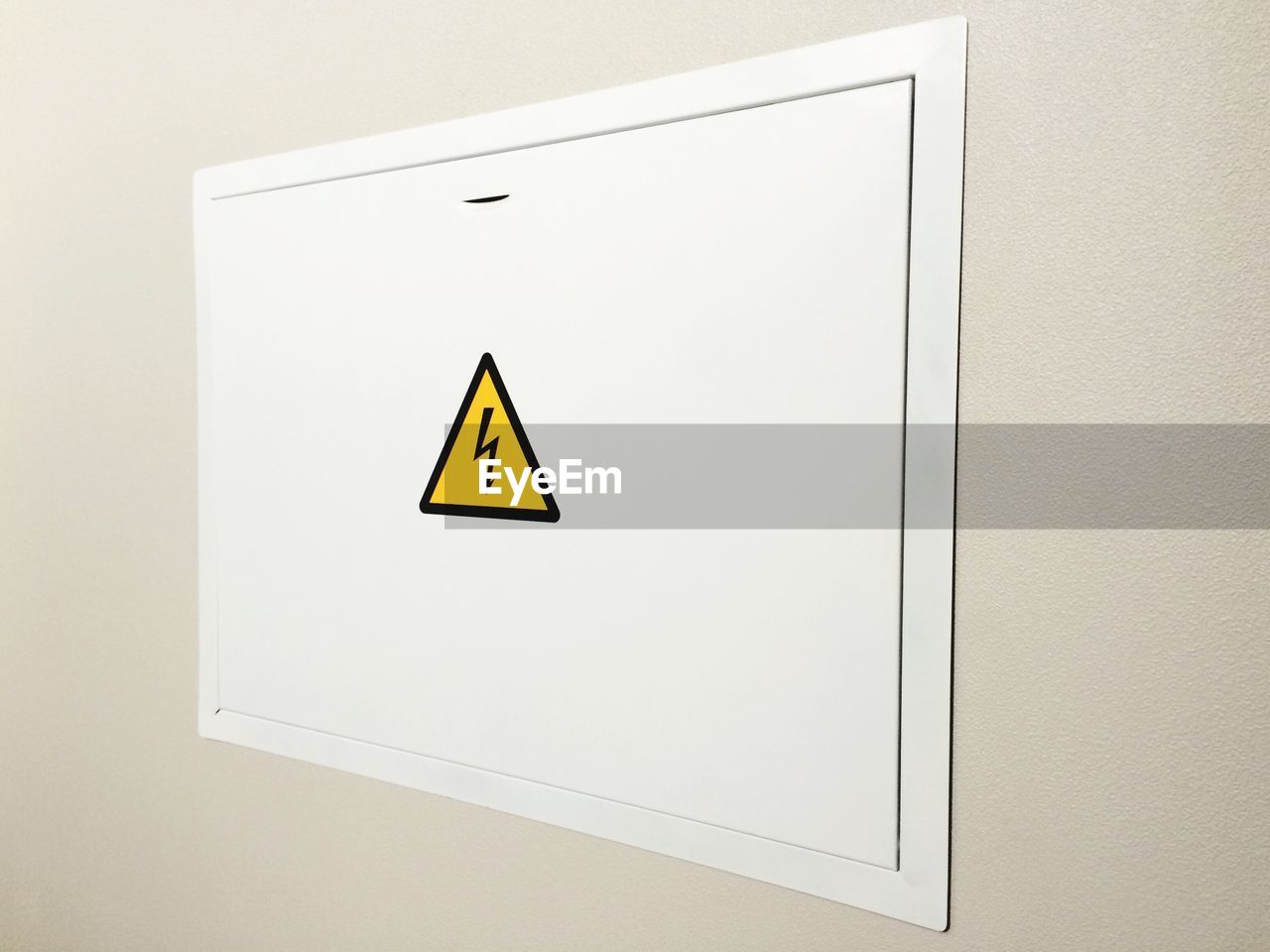 sign, communication, wall - building feature, shape, yellow, high voltage sign, geometric shape, warning sign, white color, information, wall, no people, arrow symbol, warning symbol, copy space, symbol, indoors, information sign, triangle shape, close-up, computer icon