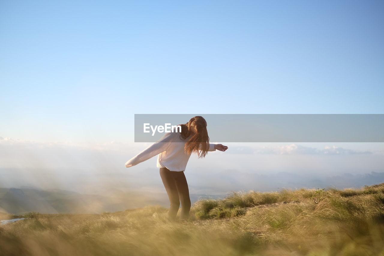 Woman On Grassy Field Against Sky