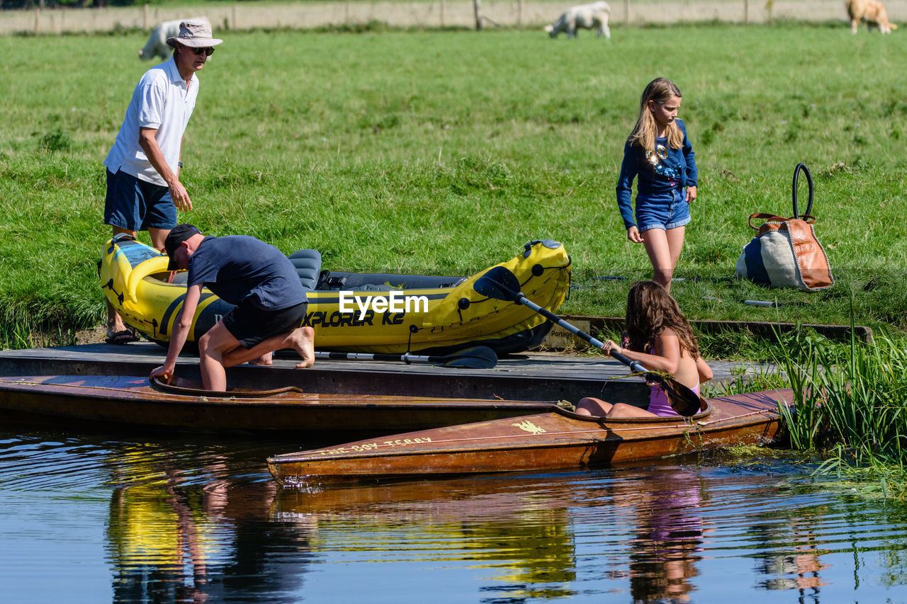 water, nautical vessel, transportation, men, day, nature, mode of transportation, full length, lifestyles, males, oar, leisure activity, people, real people, waterfront, casual clothing, group of people, adult, outdoors