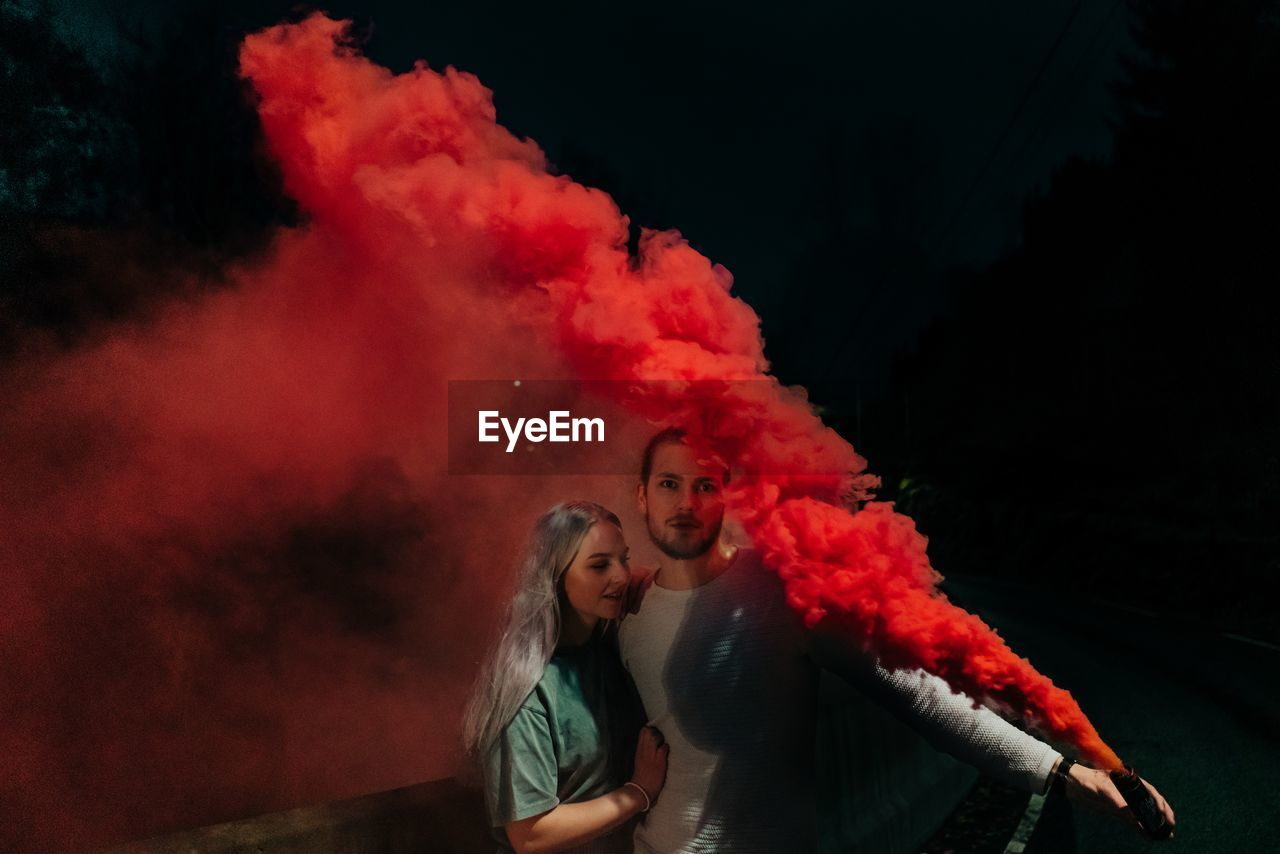 Man embracing woman while holding distress flare at night