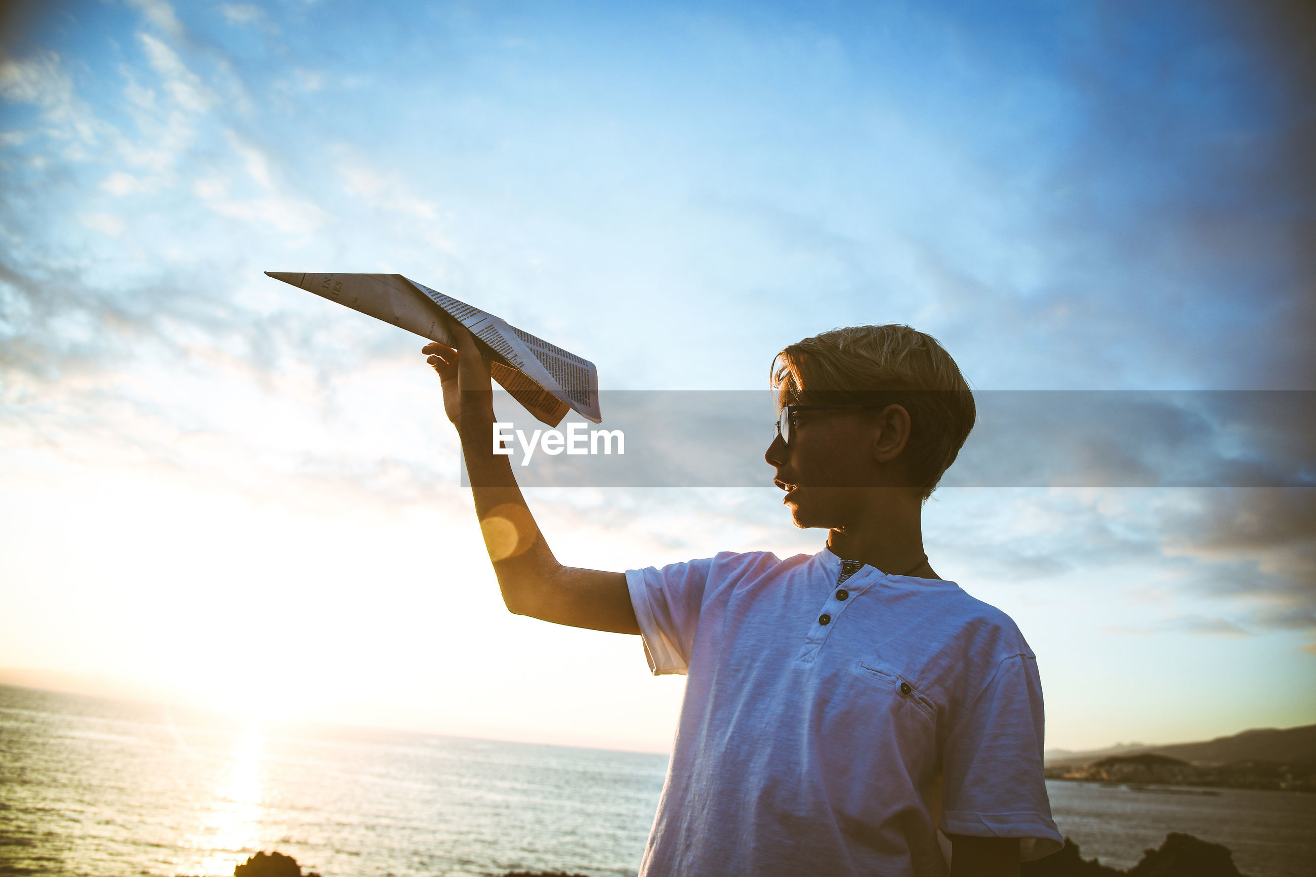 Low angle view of boy holding paper airplane against sky