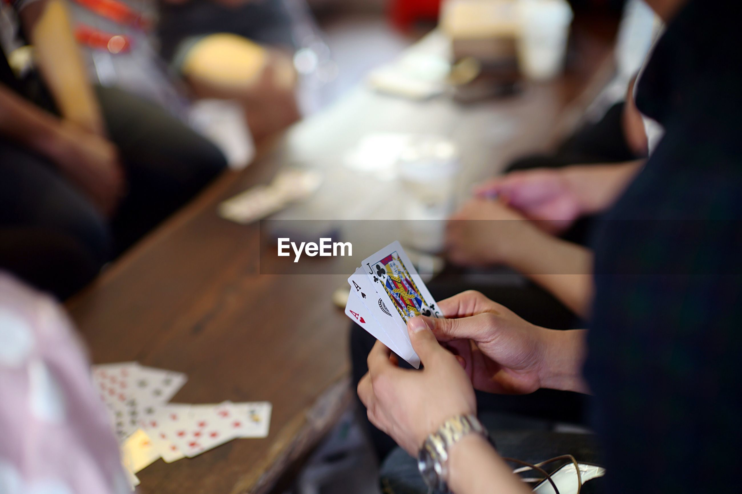 Cropped hands playing cards at table