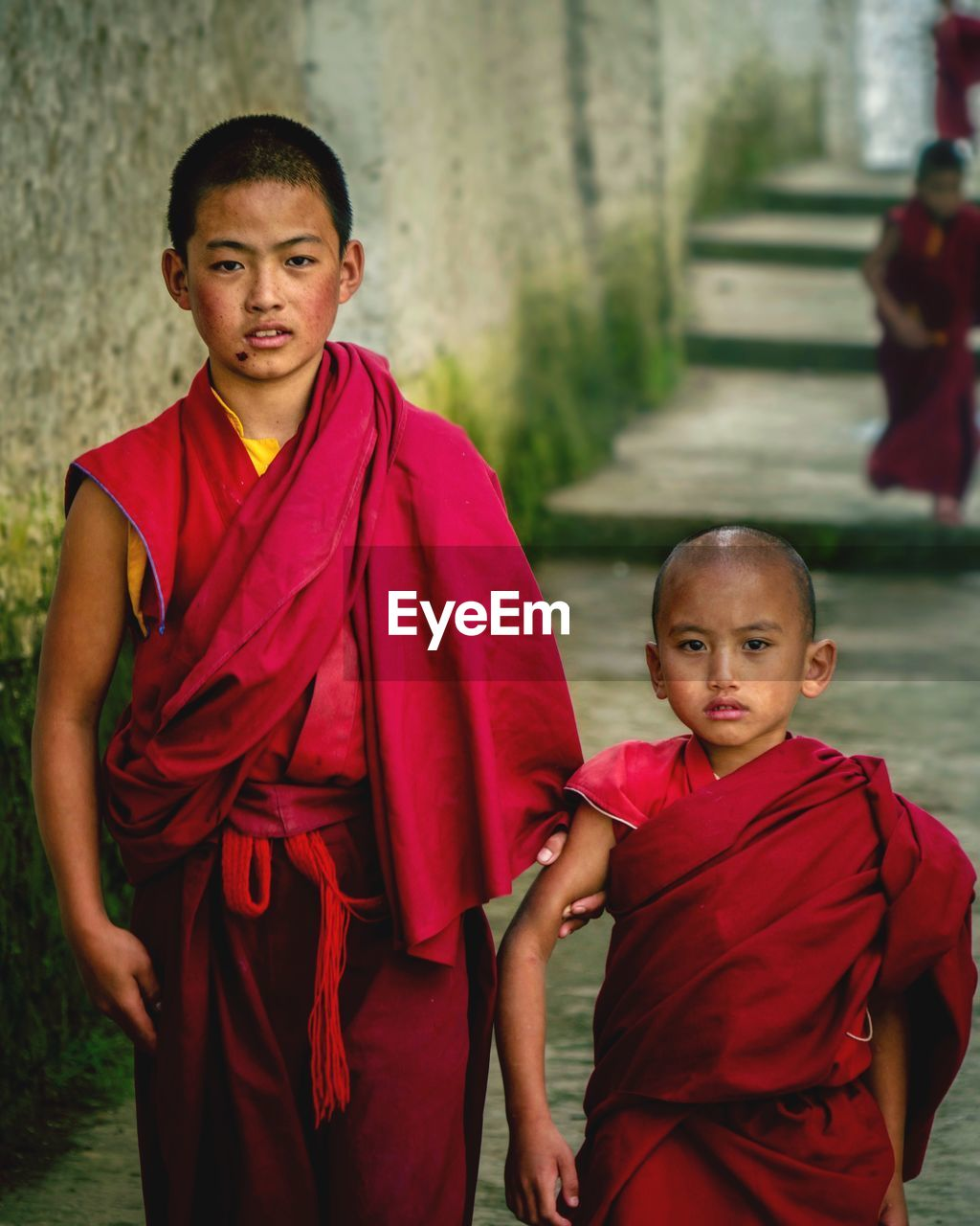real people, looking at camera, boys, red, portrait, religion, three quarter length, front view, traditional clothing, elementary age, two people, childhood, spirituality, standing, girls, togetherness, young adult, day, men, outdoors, people