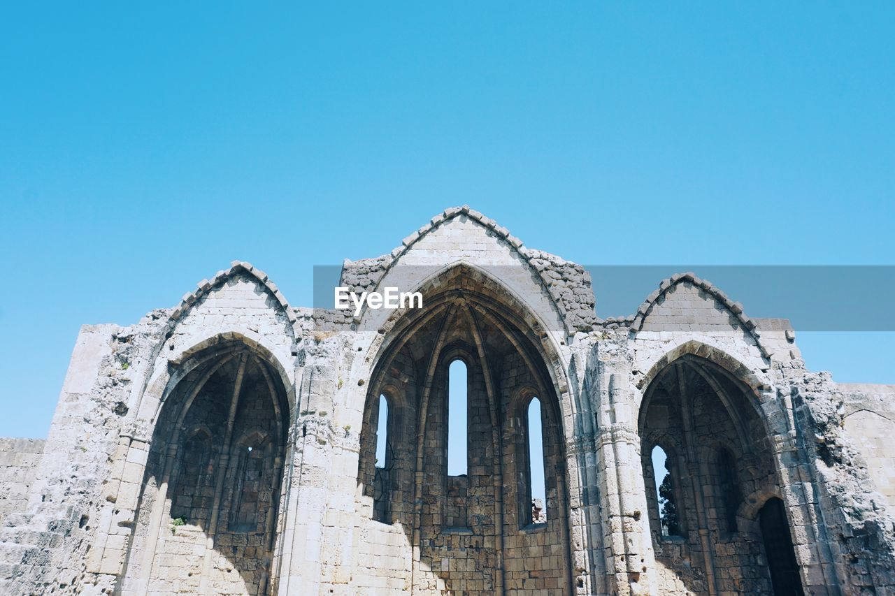 Low angle view of old ruins against clear blue sky
