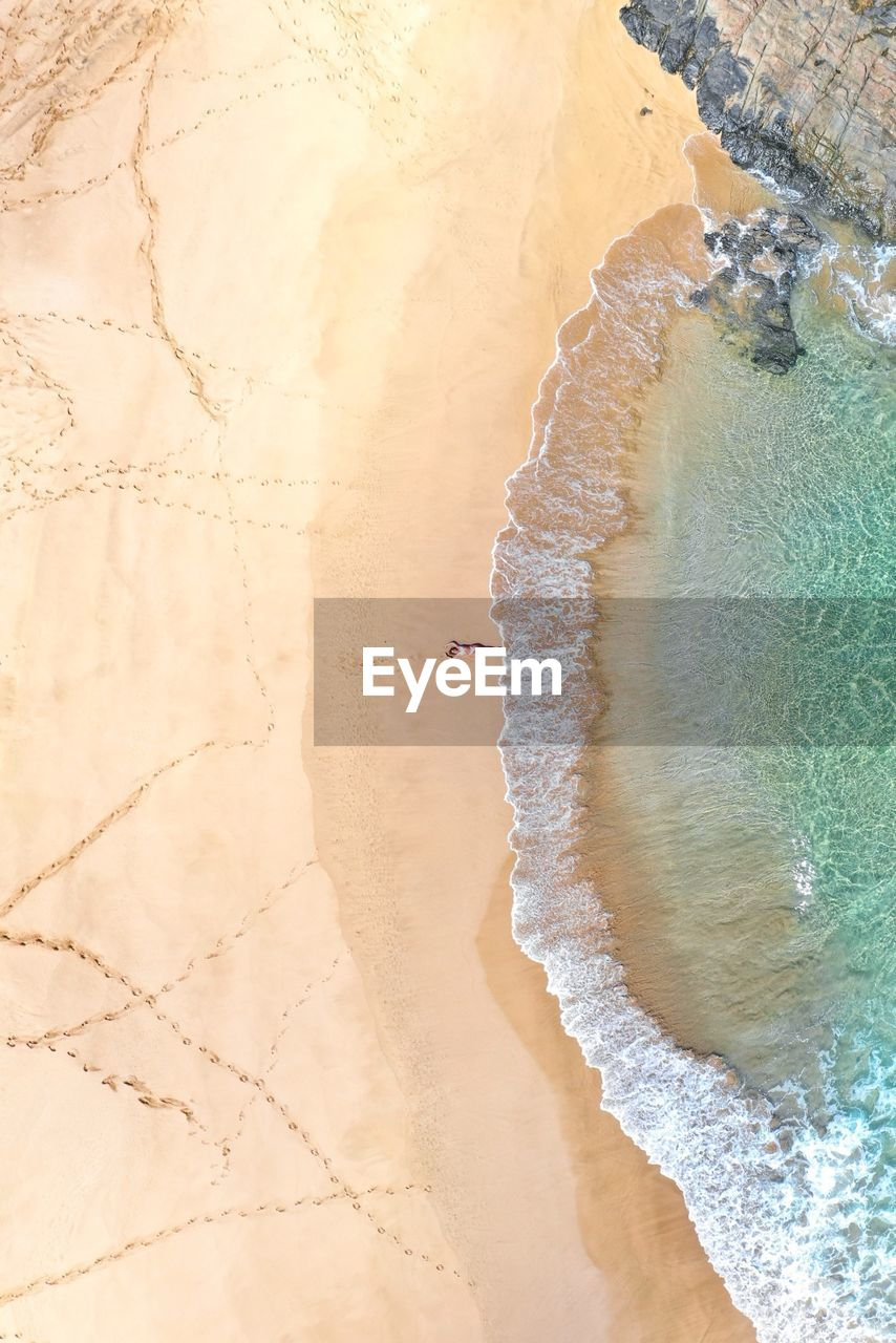 Aerial View Of Mid Adult Woman Lying At Beach