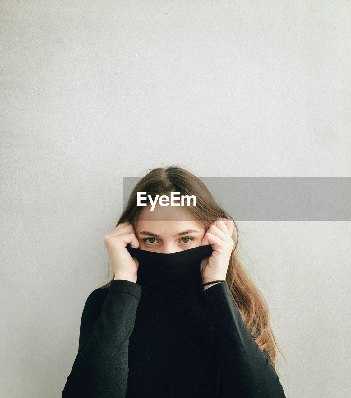 one person, portrait, looking at camera, front view, indoors, young adult, white background, young women, lifestyles, copy space, hair, wall - building feature, standing, real people, leisure activity, studio shot, casual clothing, long hair, hairstyle, obscured face, human face