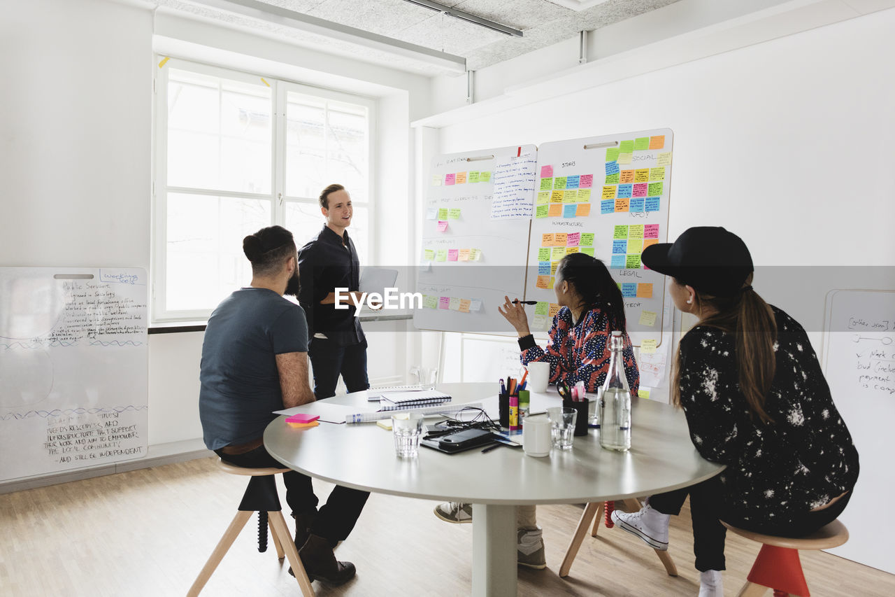 table, standing, indoors, women, office, men, cooperation, planning, three quarter length, communication, group of people, business, teamwork, males, creativity, adult, togetherness, people, strategy, casual clothing, brainstorming, coworker