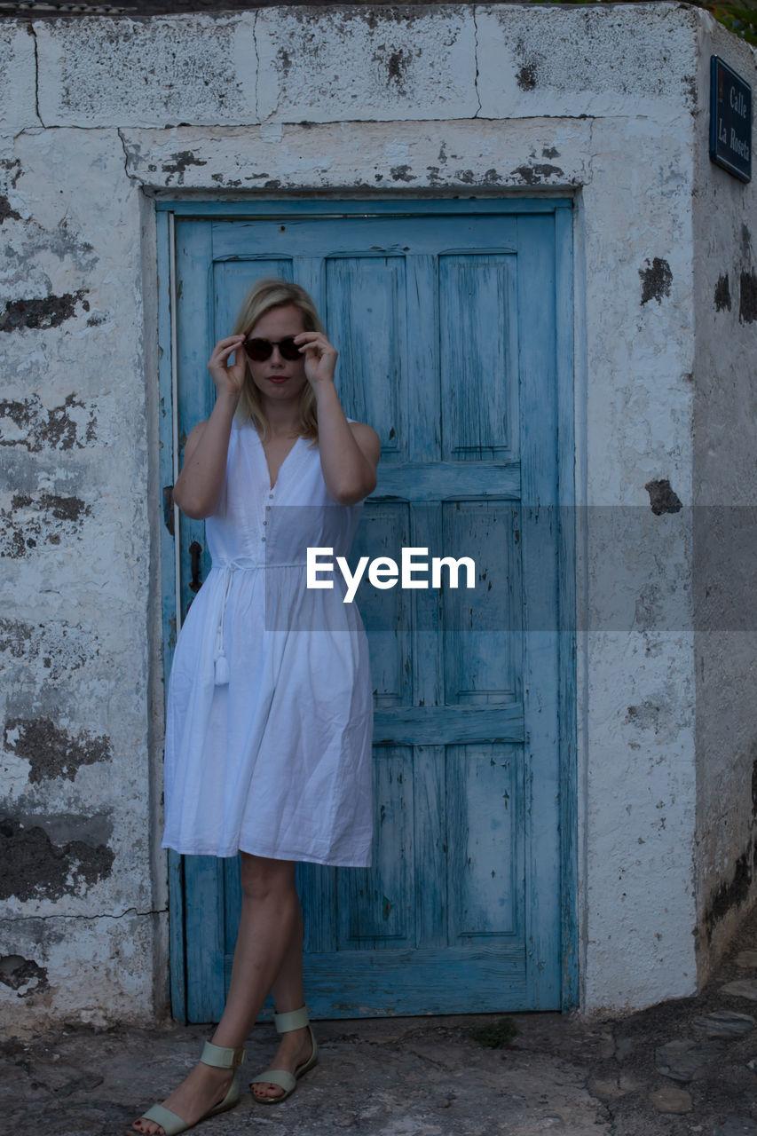 Full length portrait of woman standing by door