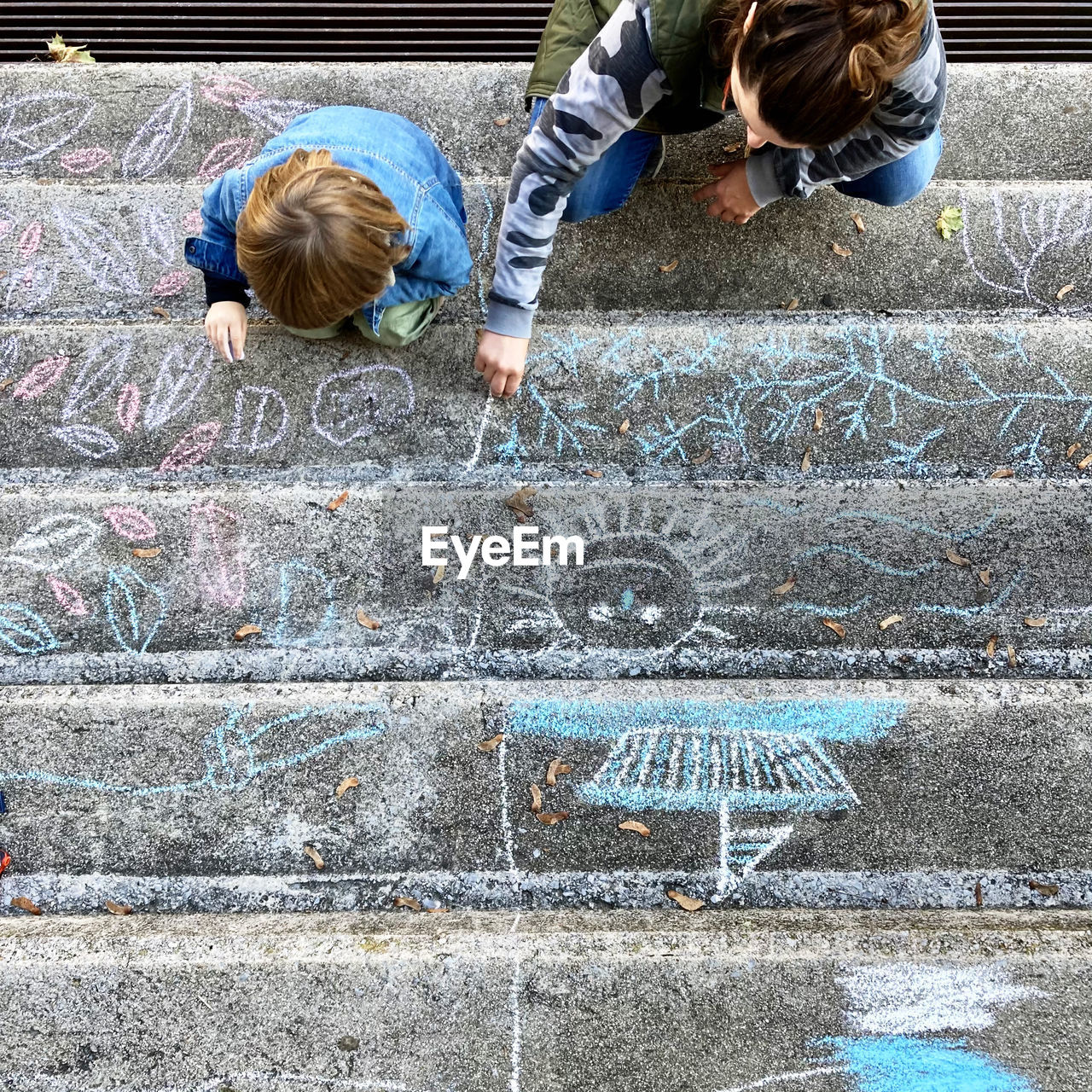 Directly above shot of mother and son drawing on steps outdoors