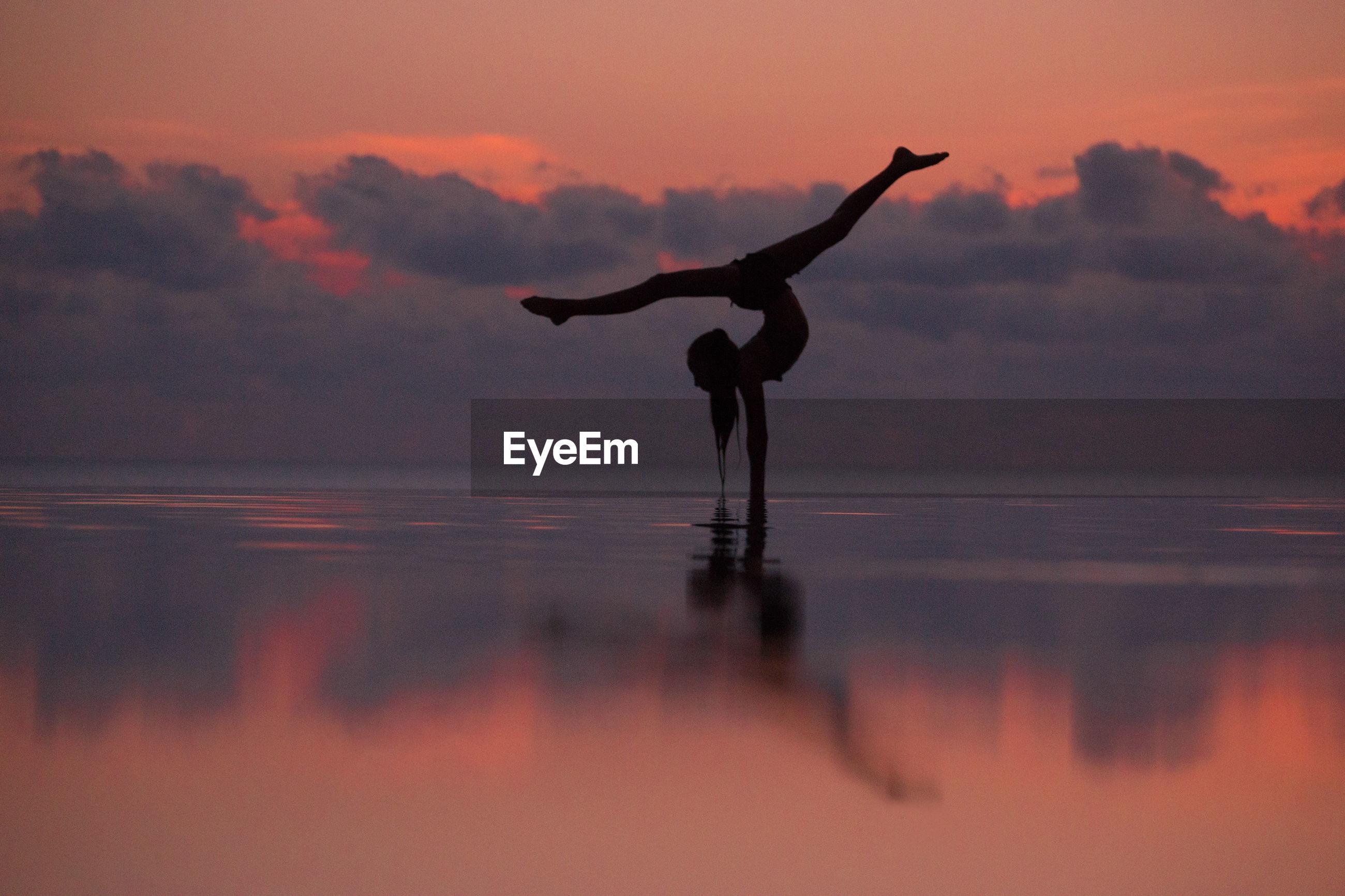 Full length of woman doing ballet dancing in infinity pool by sea against sky