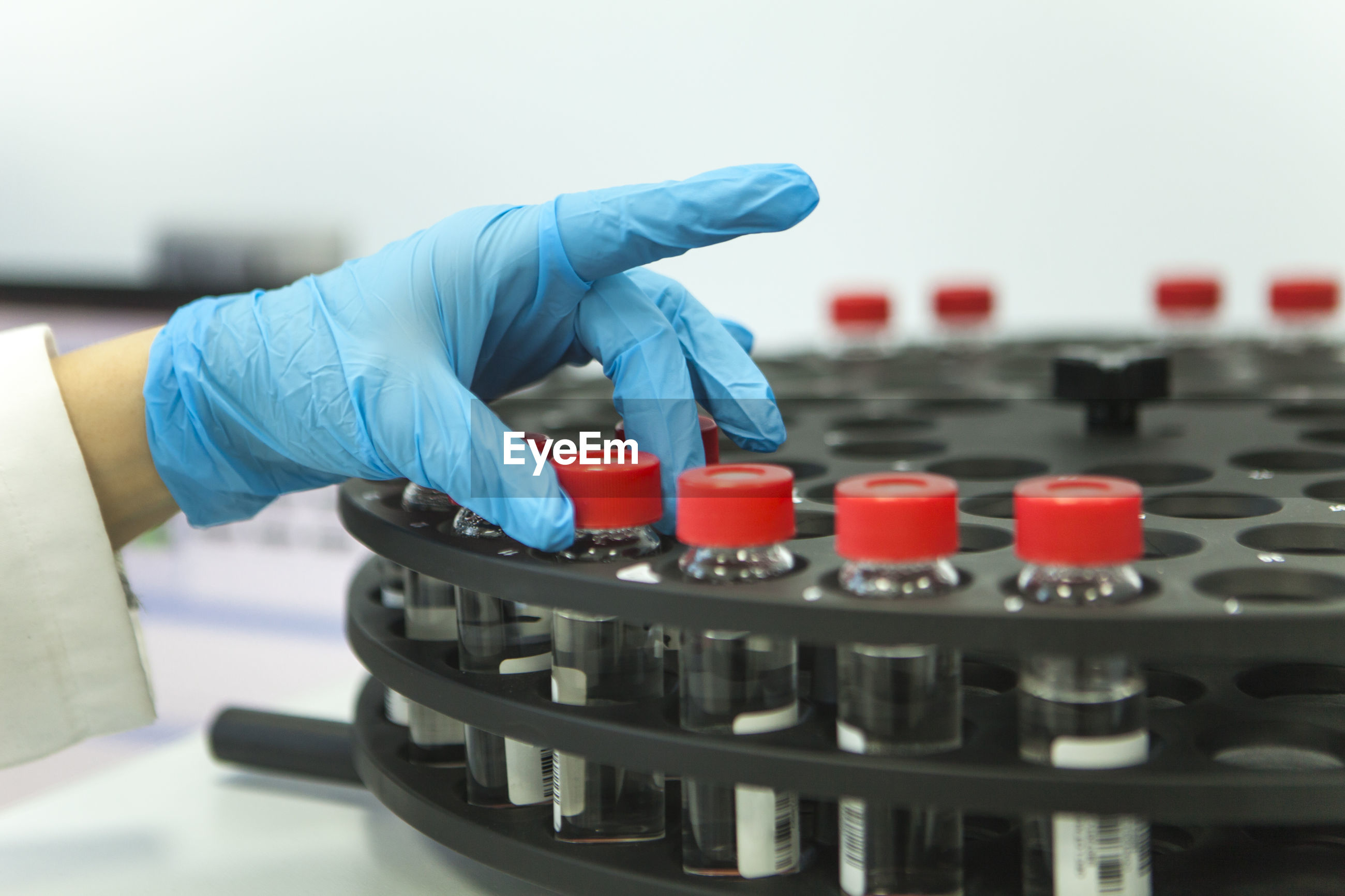 Cropped hand of scientist holding bottle in laboratory