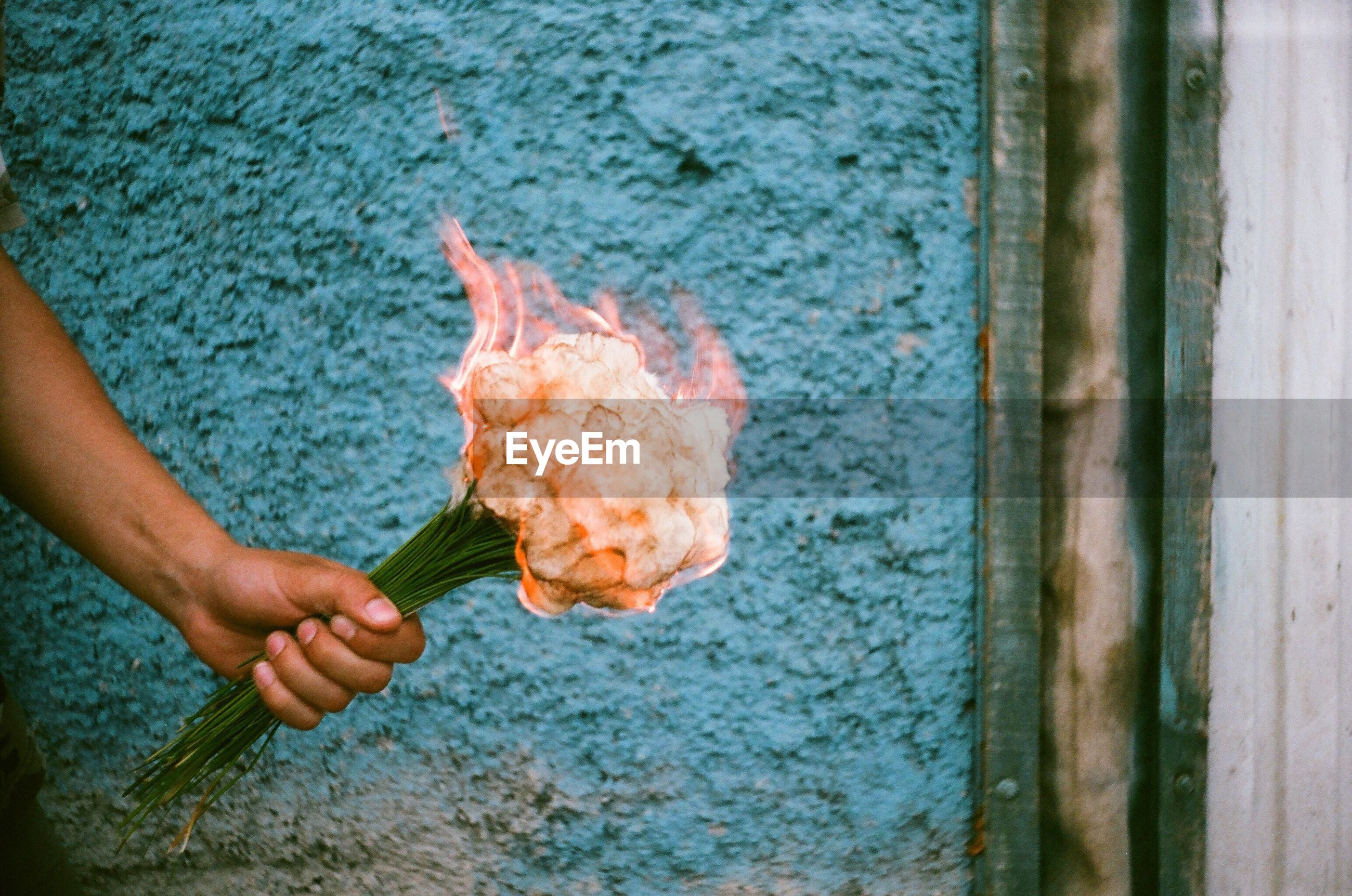 Cropped hand holding burning bouquet against blue wall