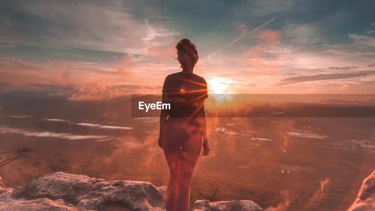 Rear View Of Woman Standing On Mountain Against Cloudy Sky During Sunset
