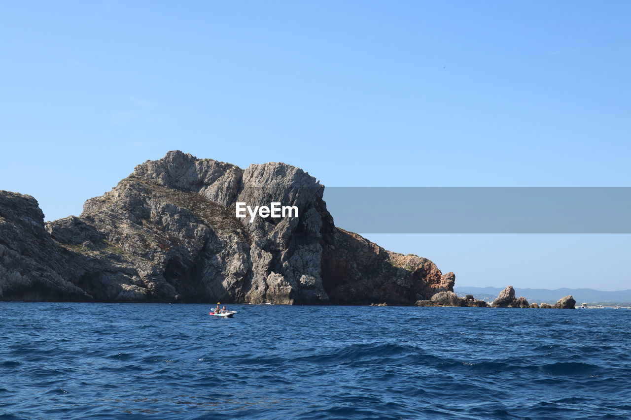 sea, water, waterfront, sky, scenics - nature, beauty in nature, nautical vessel, blue, day, clear sky, nature, rock, transportation, tranquil scene, copy space, tranquility, rock - object, mode of transportation, solid, outdoors, horizon over water