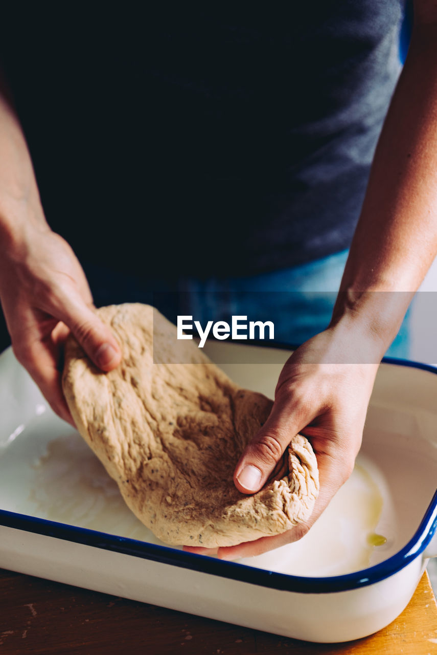 Midsection of person stretching dough in kitchen