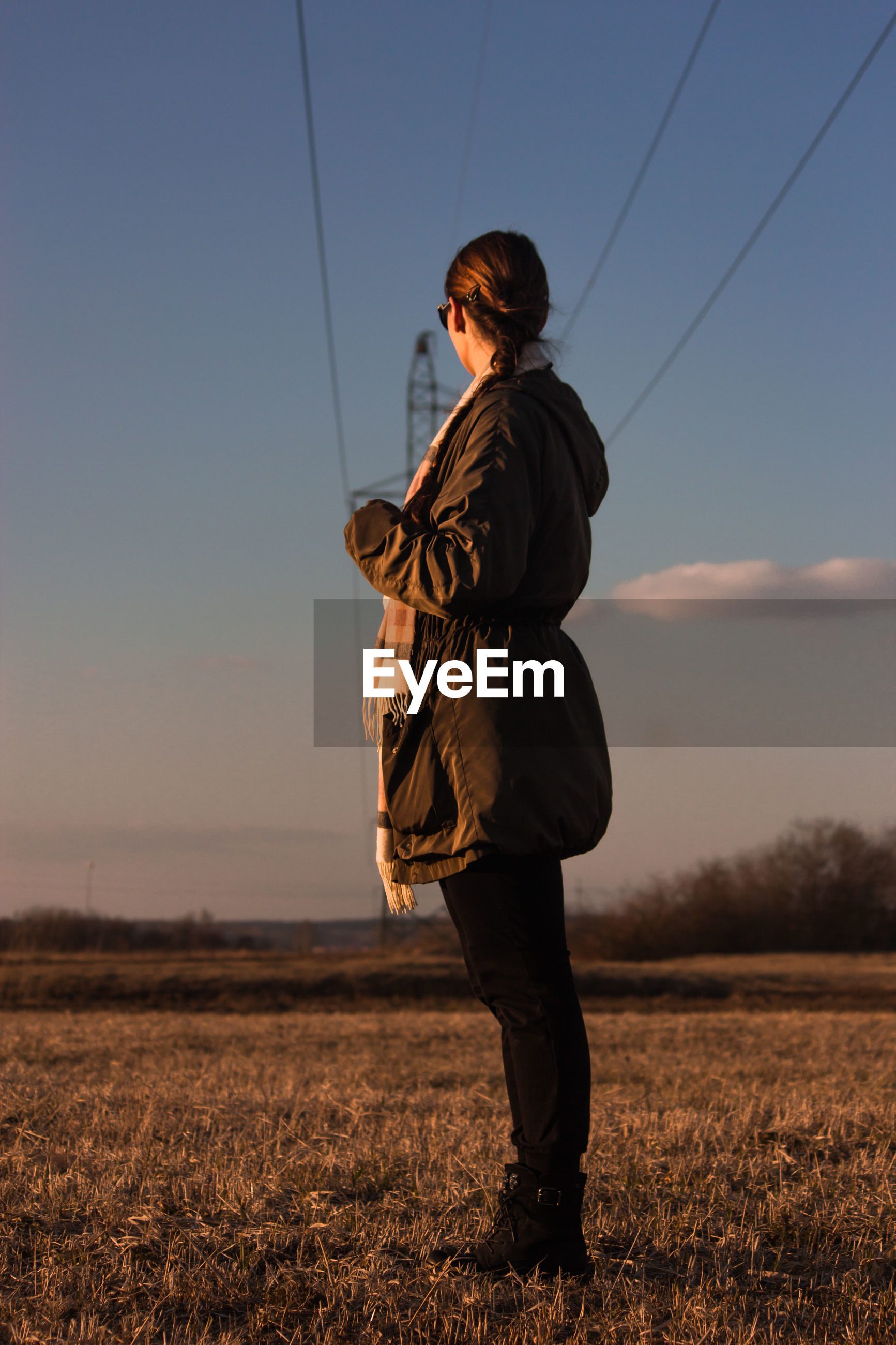 Full length side view of woman standing on land against sky during sunset