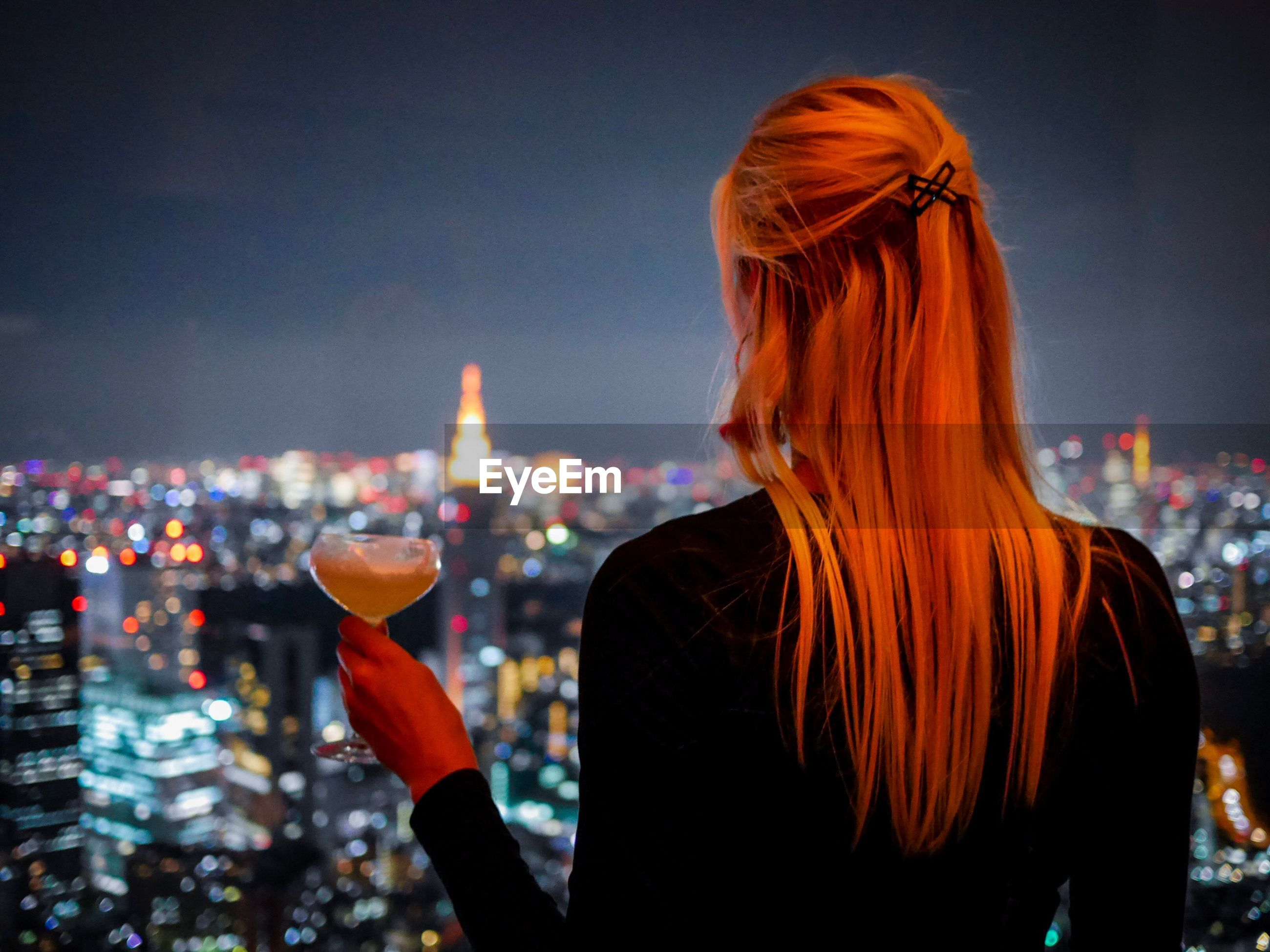Rear view of woman having drink against illuminated cityscape at night