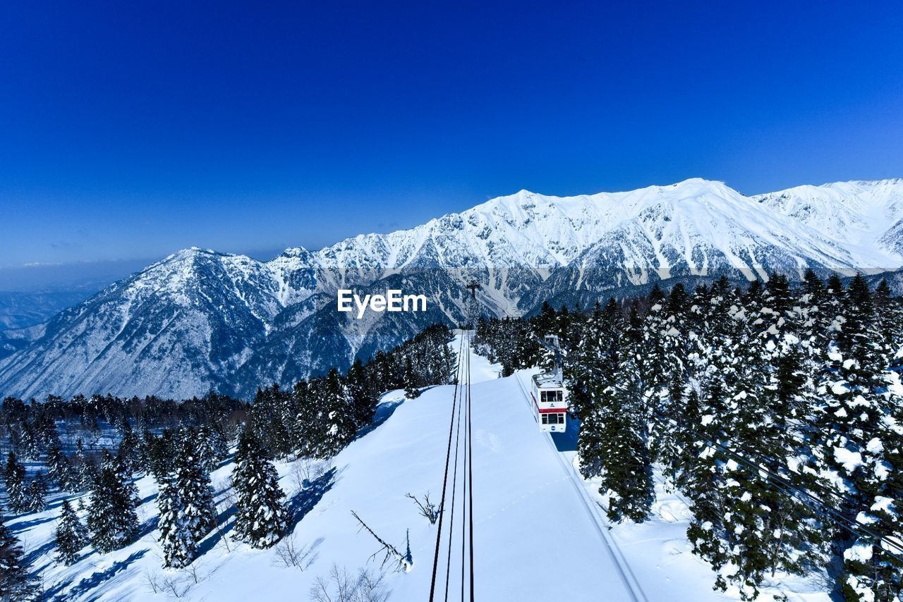 snow, winter, cold temperature, transportation, mountain, nature, scenics, beauty in nature, blue, weather, snowcapped mountain, outdoors, mode of transport, day, sky, no people, mountain range, landscape, tree, clear sky