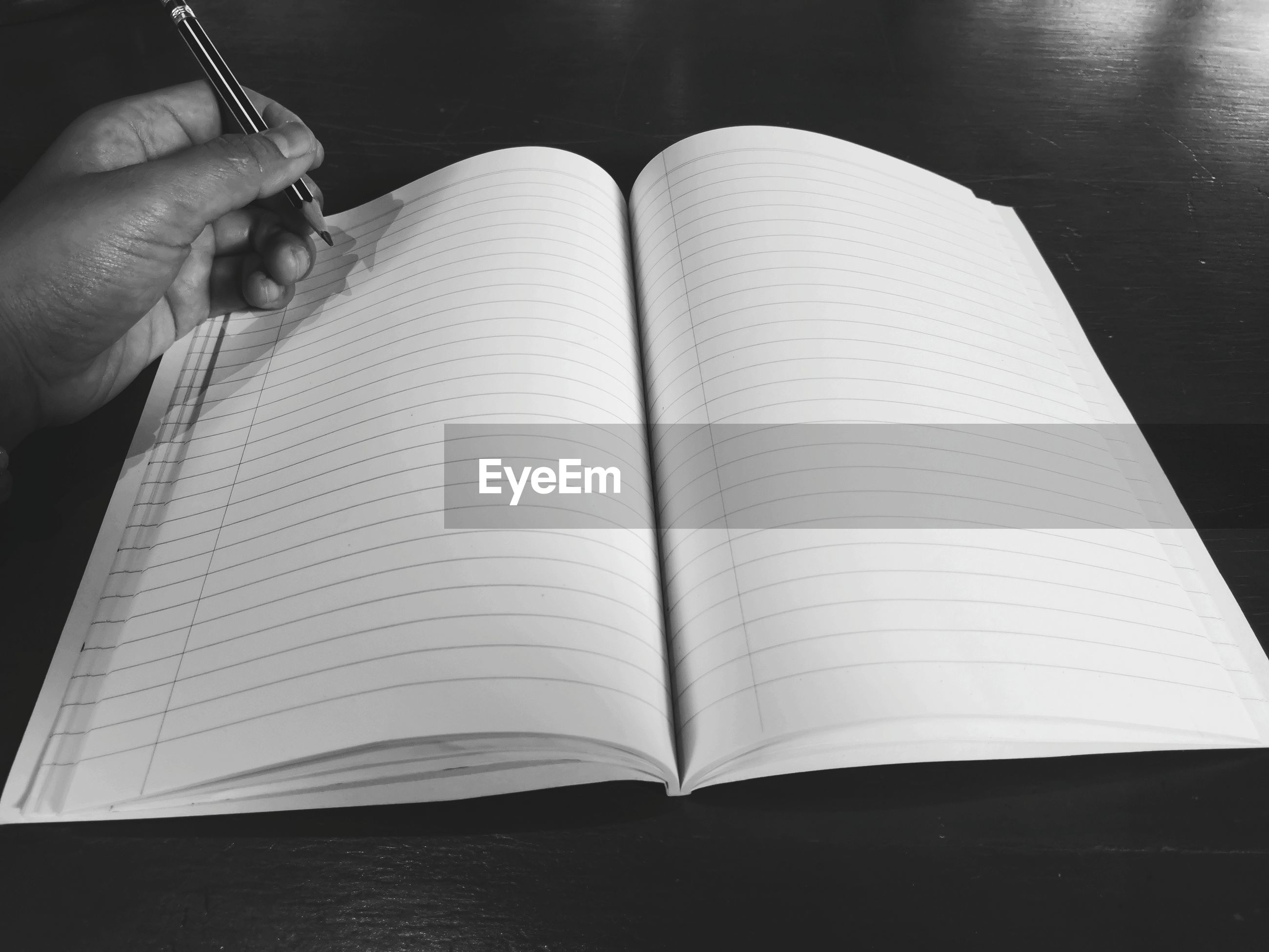 Cropped hand of person holding pencil over book on table