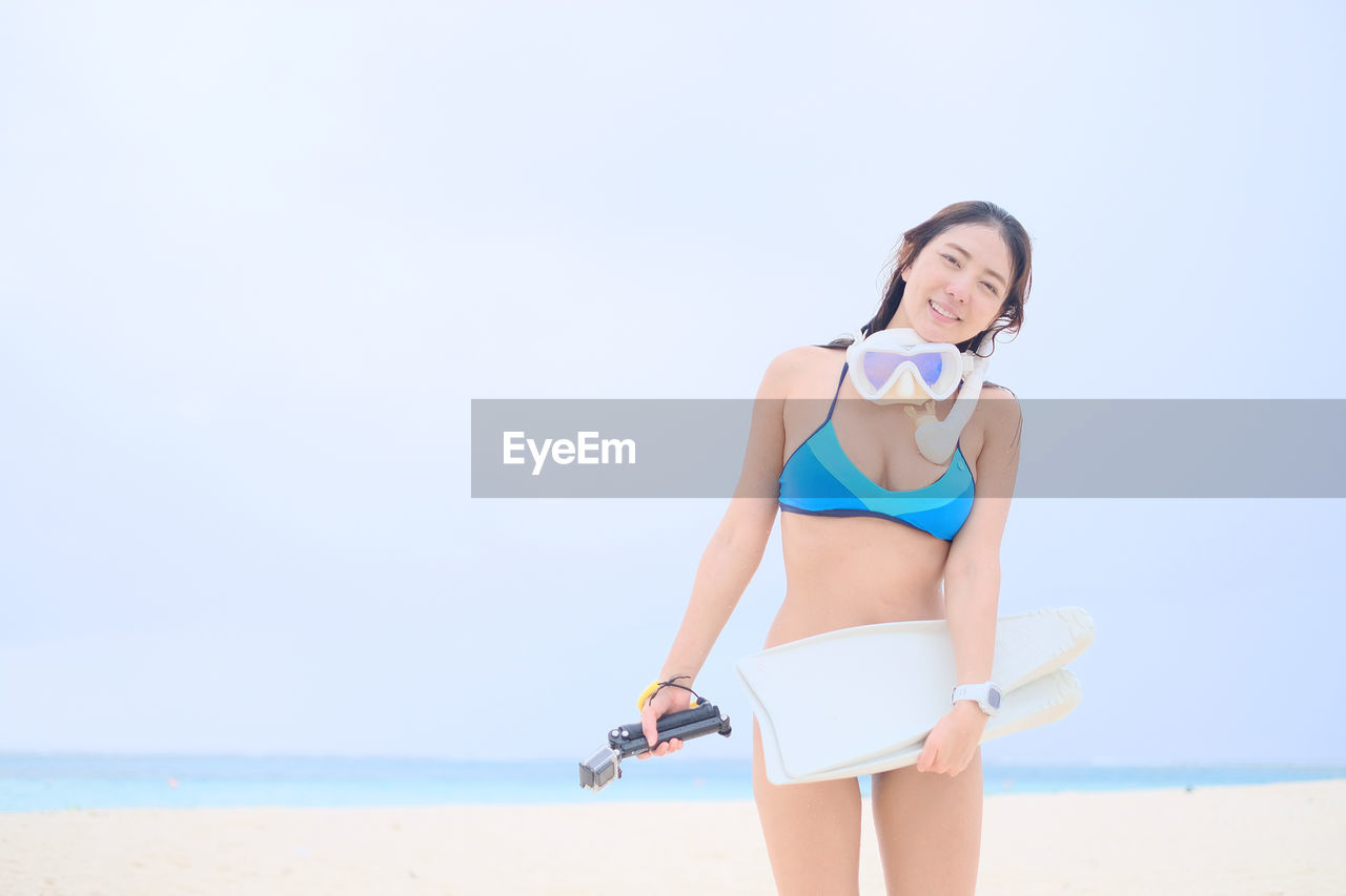 Portrait Of Young Woman In Bikini Standing At Beach Against Sky