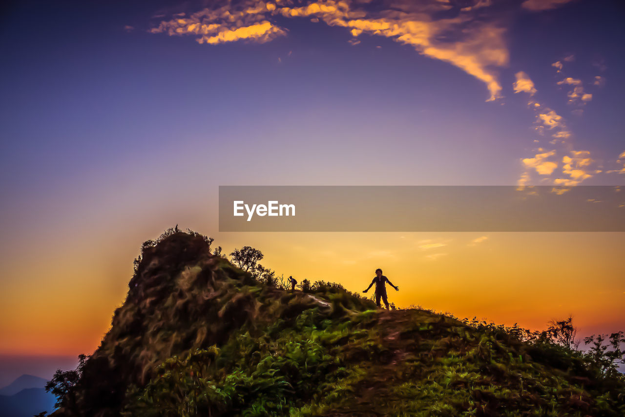 Low angle view of hiker standing on mountain against sky during sunset