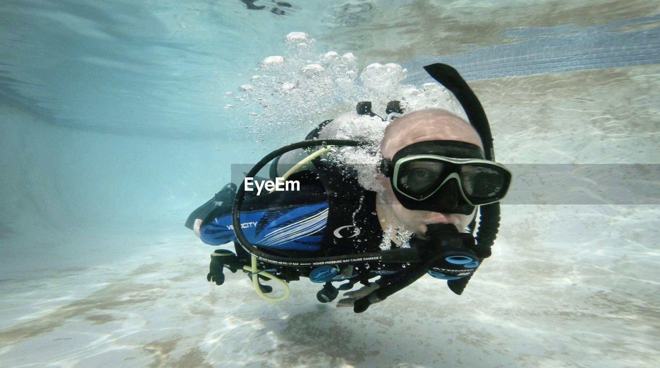 Close-up of man scuba diving in sea