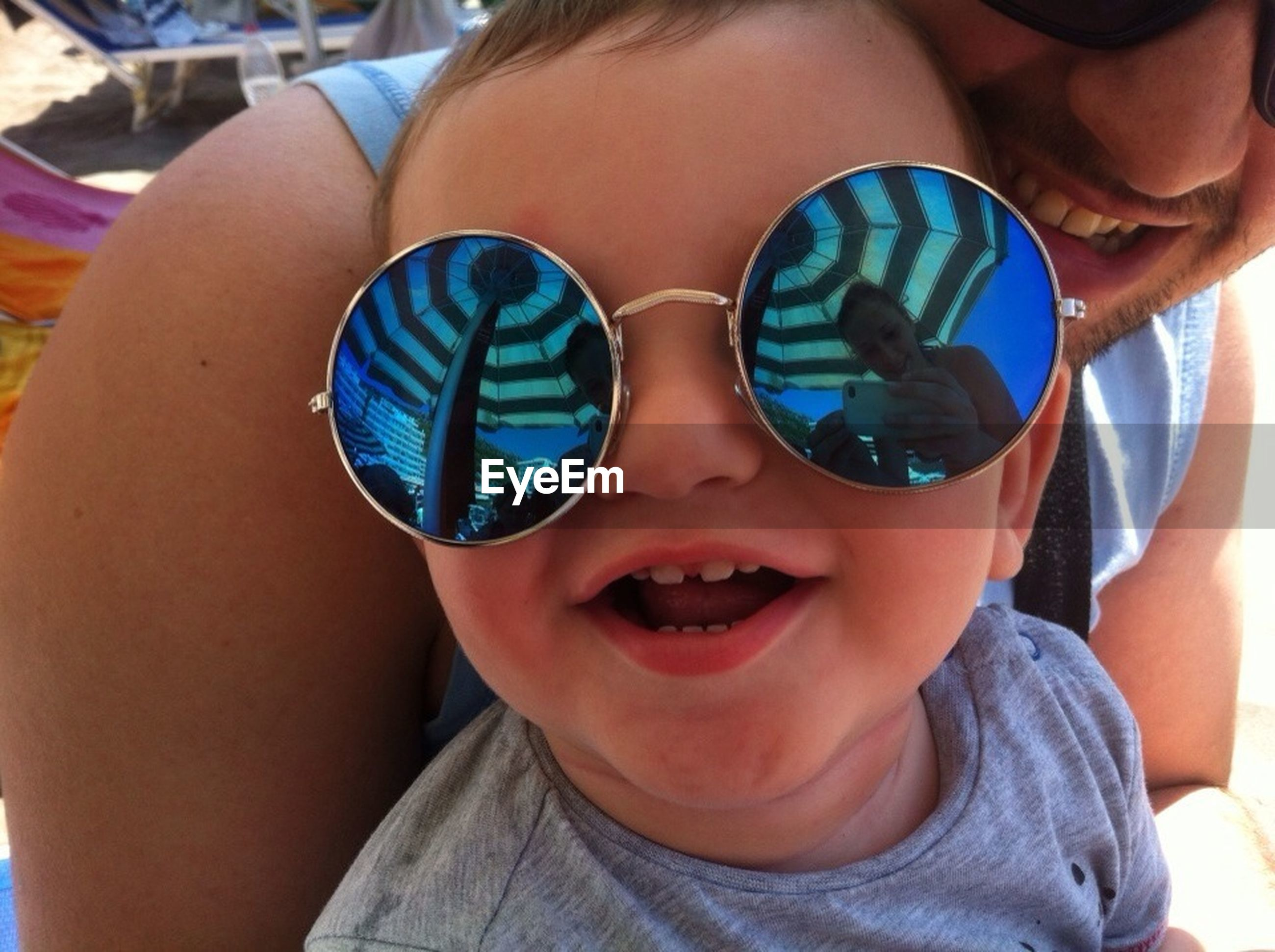 lifestyles, leisure activity, person, sunglasses, looking at camera, portrait, headshot, holding, front view, smiling, close-up, childhood, boys, young adult, happiness, focus on foreground, elementary age, reflection