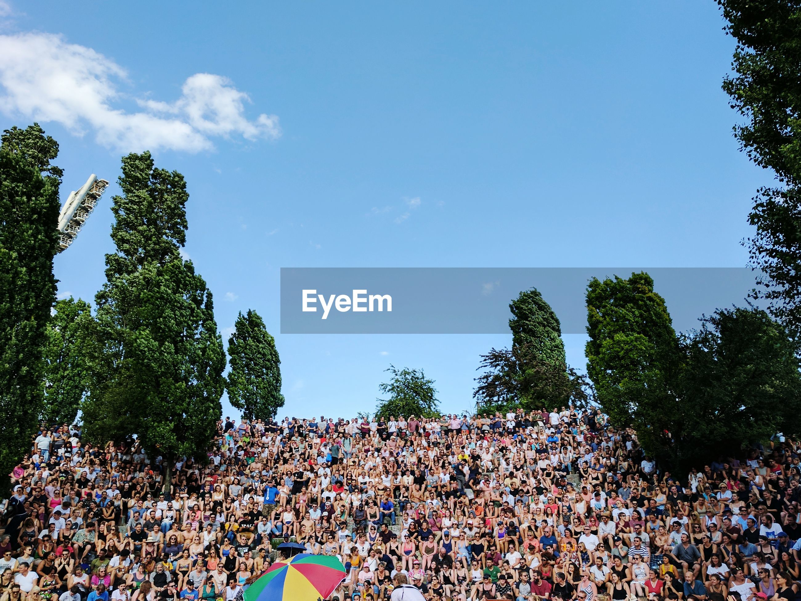Audience at mauerpark against sky