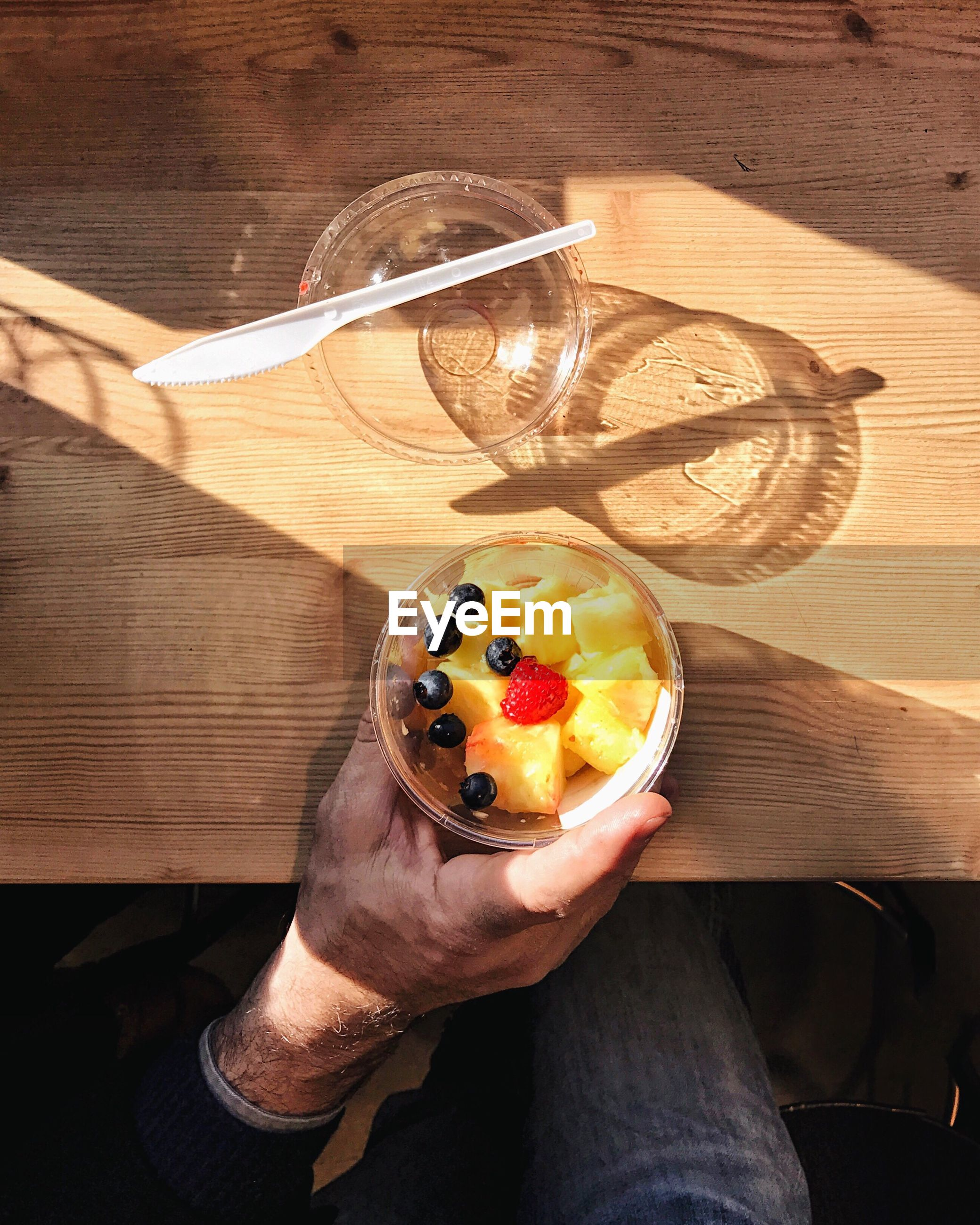 High angle view of hand holding fruit in a cup