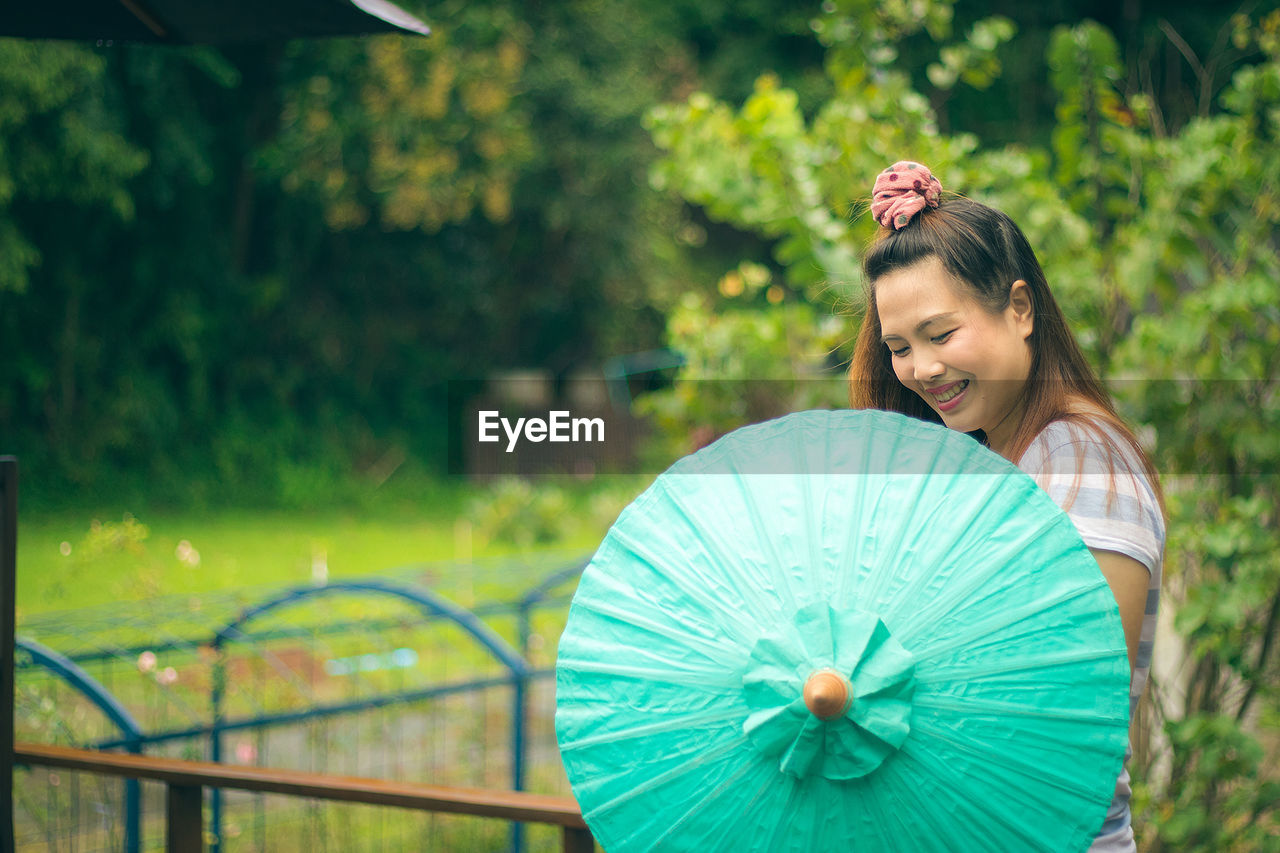 Side view of cheerful woman with turquoise umbrella at park