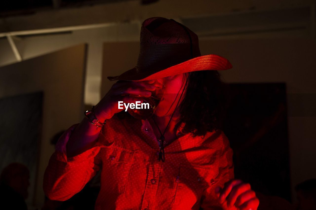 red, one person, clothing, real people, waist up, indoors, lifestyles, unrecognizable person, focus on foreground, standing, hat, leisure activity, disguise, obscured face, celebration, front view, costume, mask, home interior, dark, hood - clothing, hairstyle