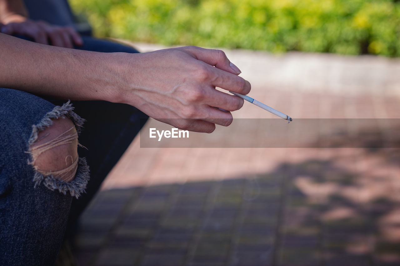 Cropped image of man smoking cigarette while sitting outdoors