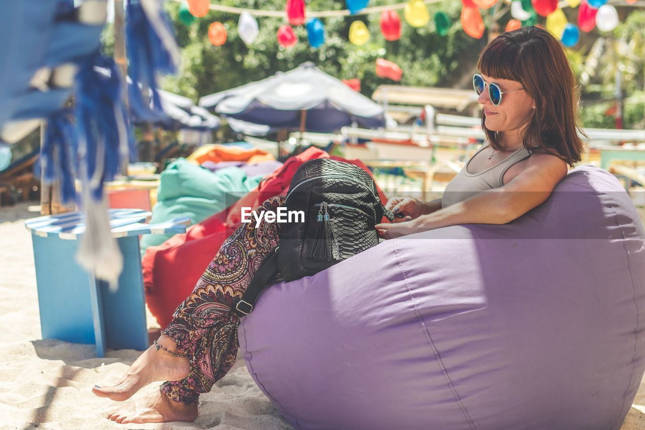 Smiling Young Woman Wearing Sunglasses While Sitting On Bean Bag At Beach