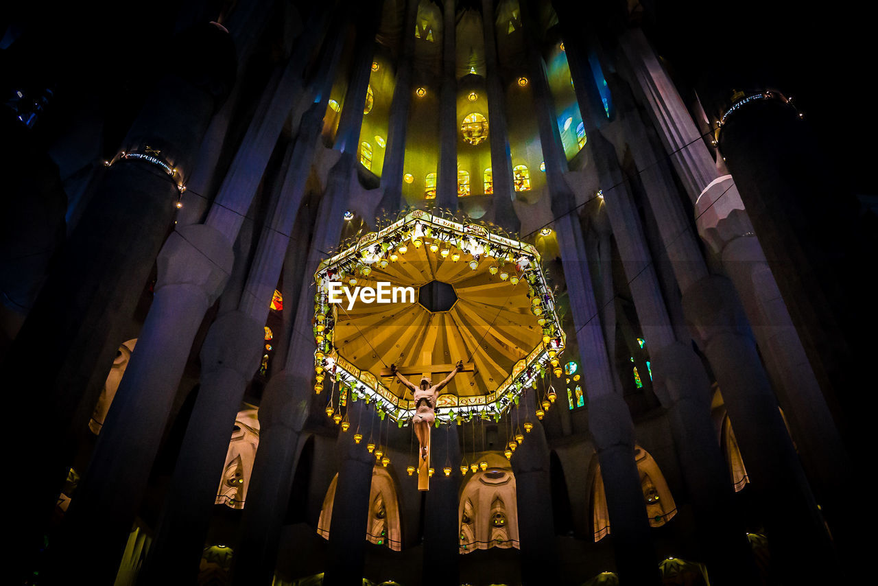 illuminated, religion, low angle view, place of worship, hanging, spirituality, no people, indoors, architecture, day