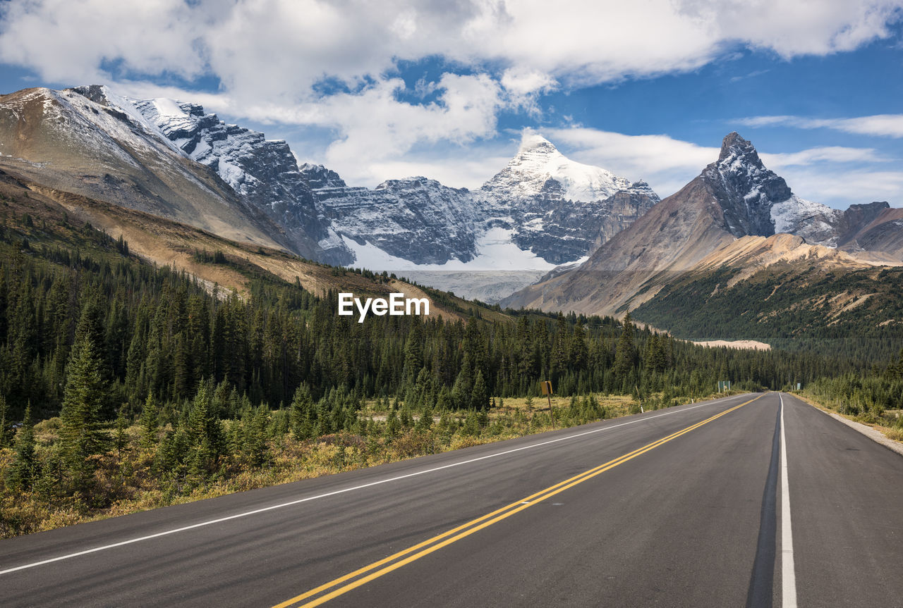 mountain, road, sky, transportation, cloud - sky, scenics - nature, marking, direction, symbol, road marking, beauty in nature, the way forward, mountain range, sign, no people, tranquil scene, nature, tranquility, non-urban scene, day, diminishing perspective, double yellow line, snowcapped mountain, dividing line, formation