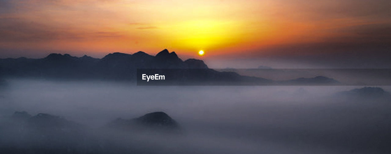 sky, scenics - nature, fog, cloud - sky, mountain, sunset, tranquil scene, tranquility, beauty in nature, nature, environment, dramatic sky, mountain range, panoramic, no people, landscape, idyllic, sun, orange color, outdoors, mountain peak, romantic sky