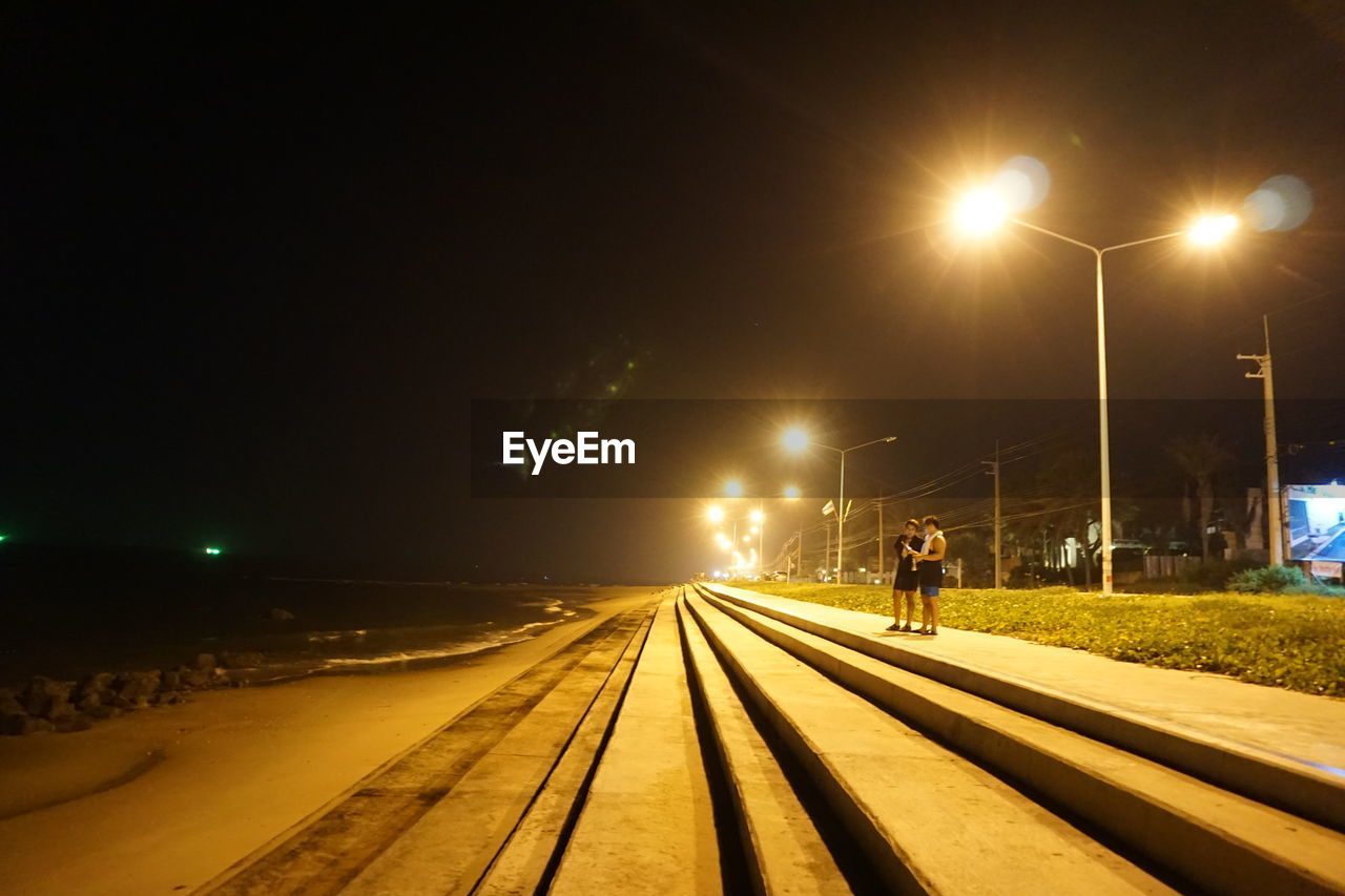 illuminated, street light, transportation, railroad track, rail transportation, track, lighting equipment, street, night, sky, direction, nature, the way forward, real people, mode of transportation, lifestyles, diminishing perspective, city, outdoors, one person, electricity, waiting