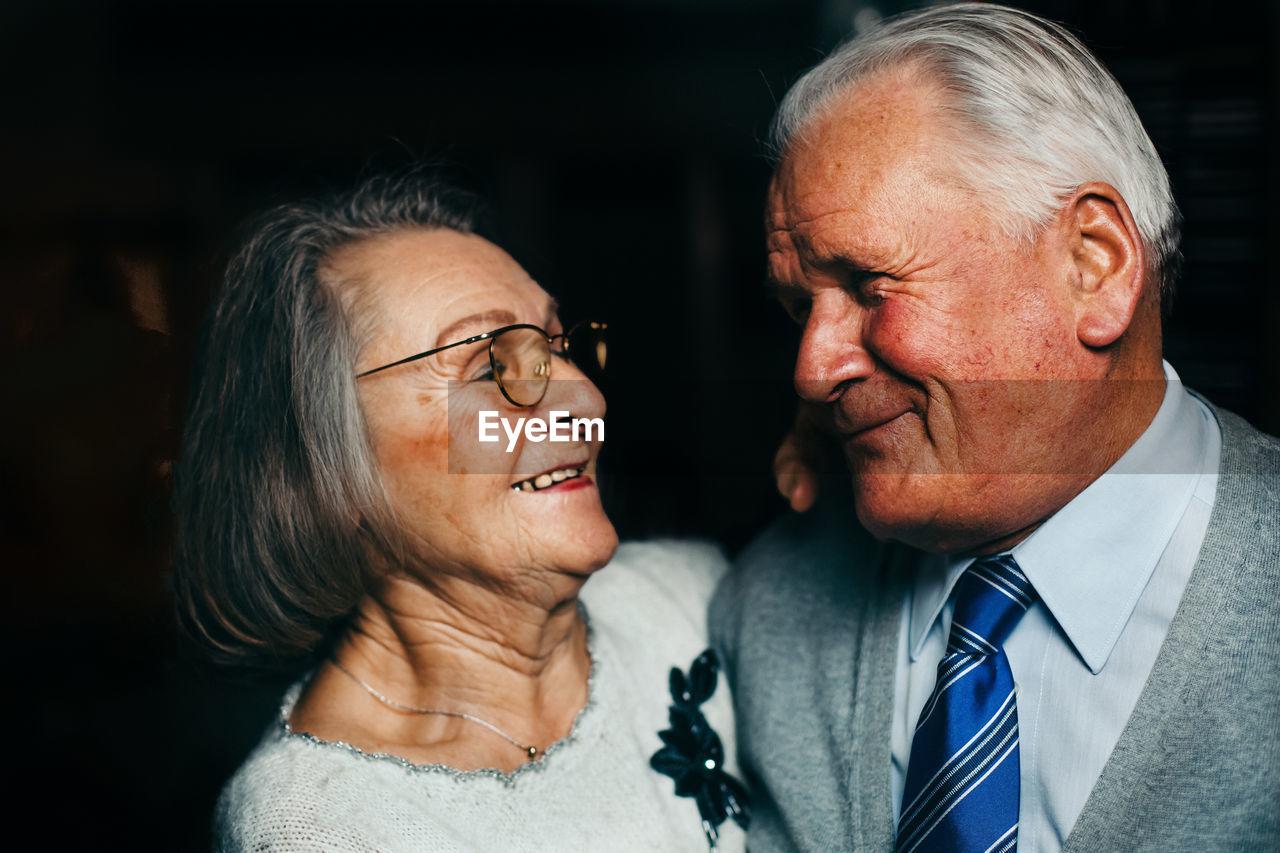 Close-up of senior couple smiling in darkroom