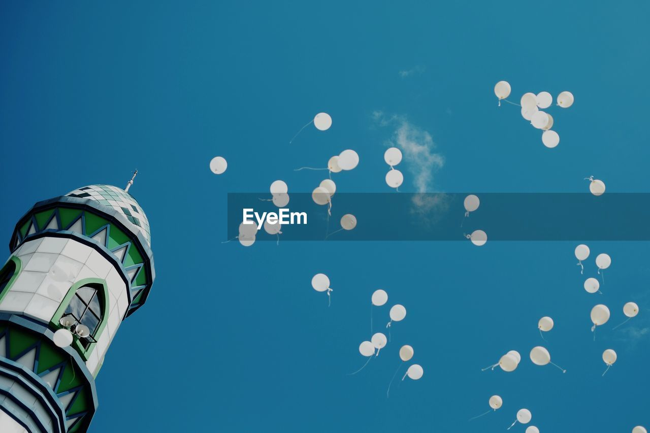 Low Angle View Of Building By Balloons Against Clear Blue Sky