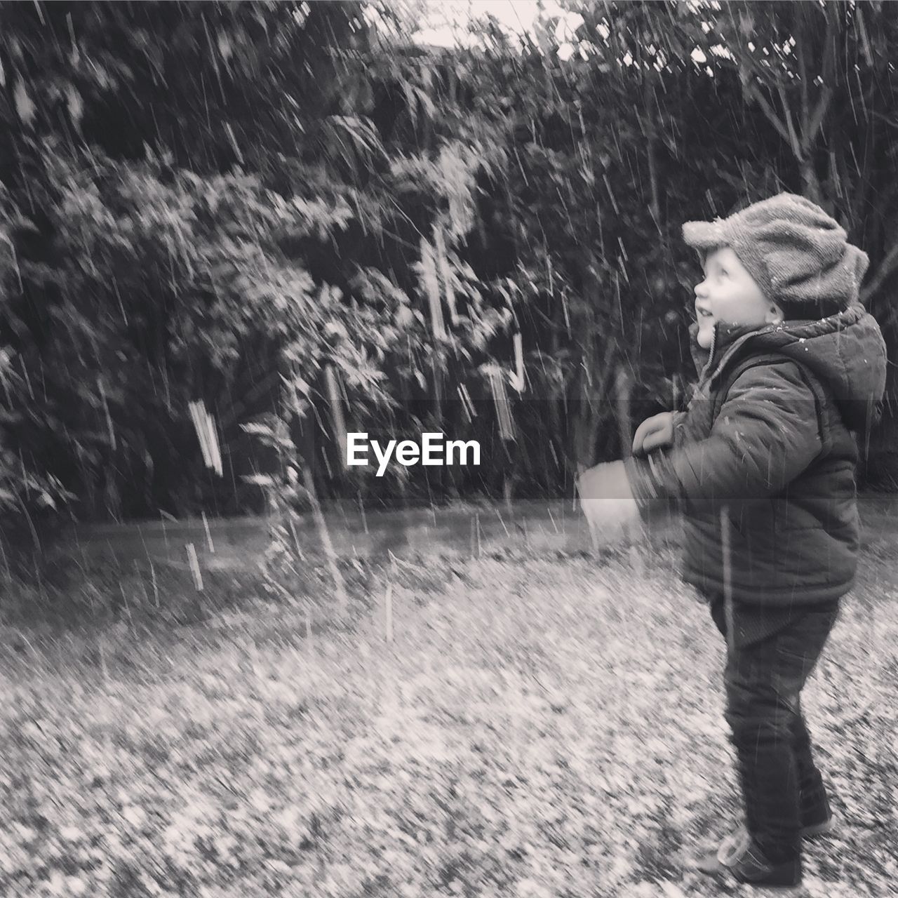 Cute boy enjoying snowfall outdoors