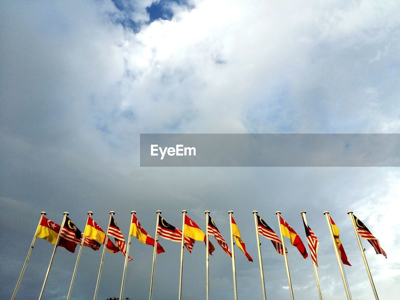 Low angle view of flags against cloudy sky